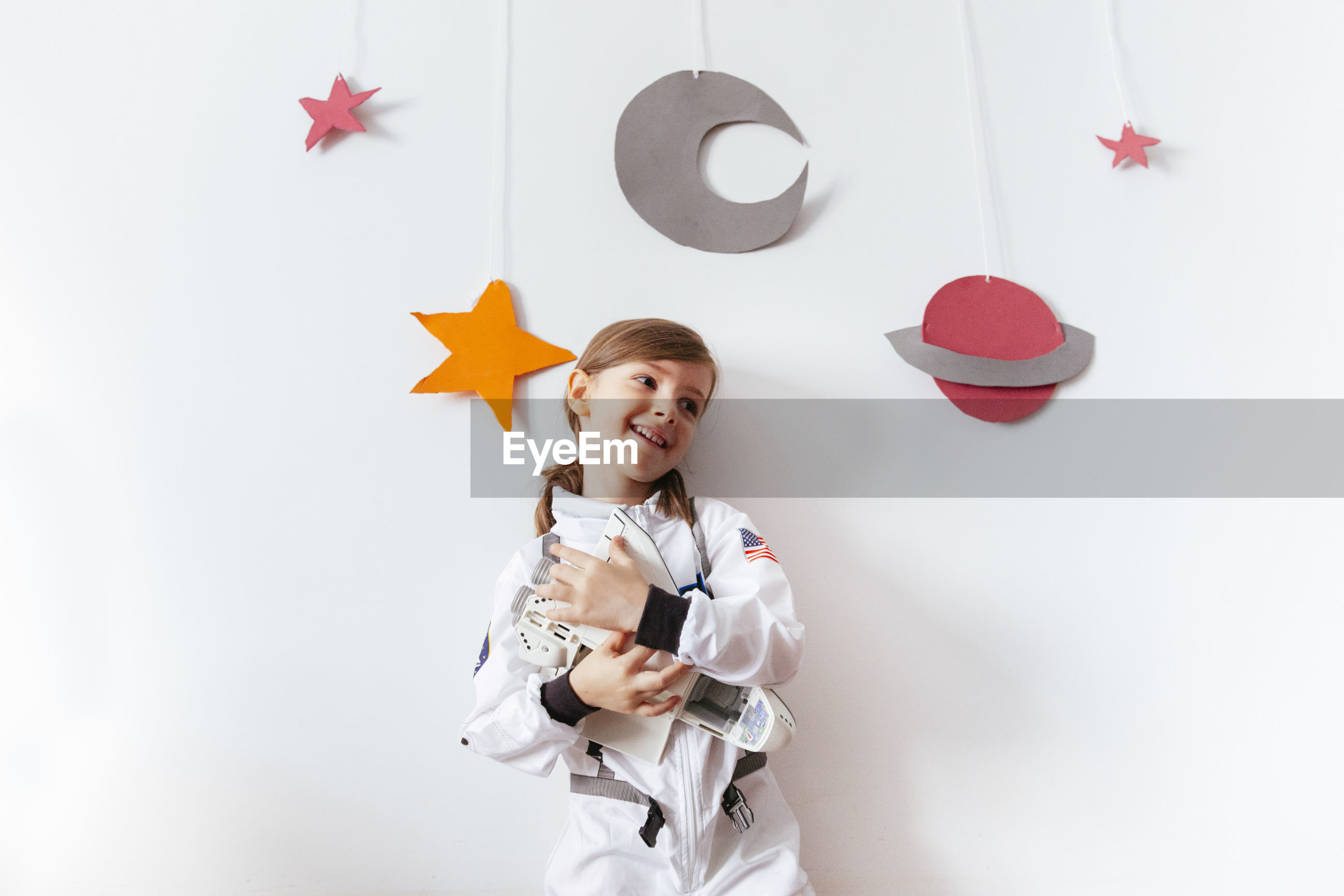 Smiling girl wearing spacesuit holding model airplane against wall at home