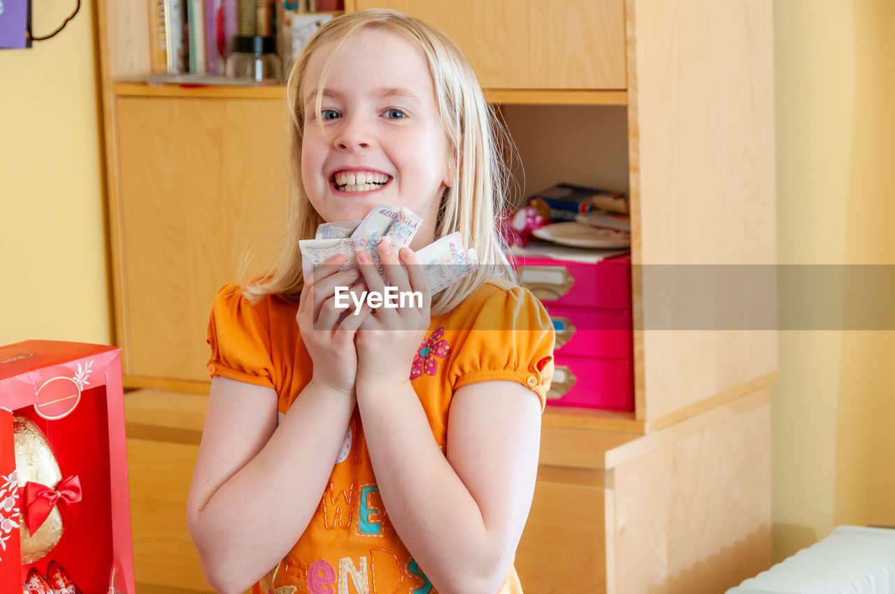 PORTRAIT OF SMILING GIRL HOLDING INDOORS