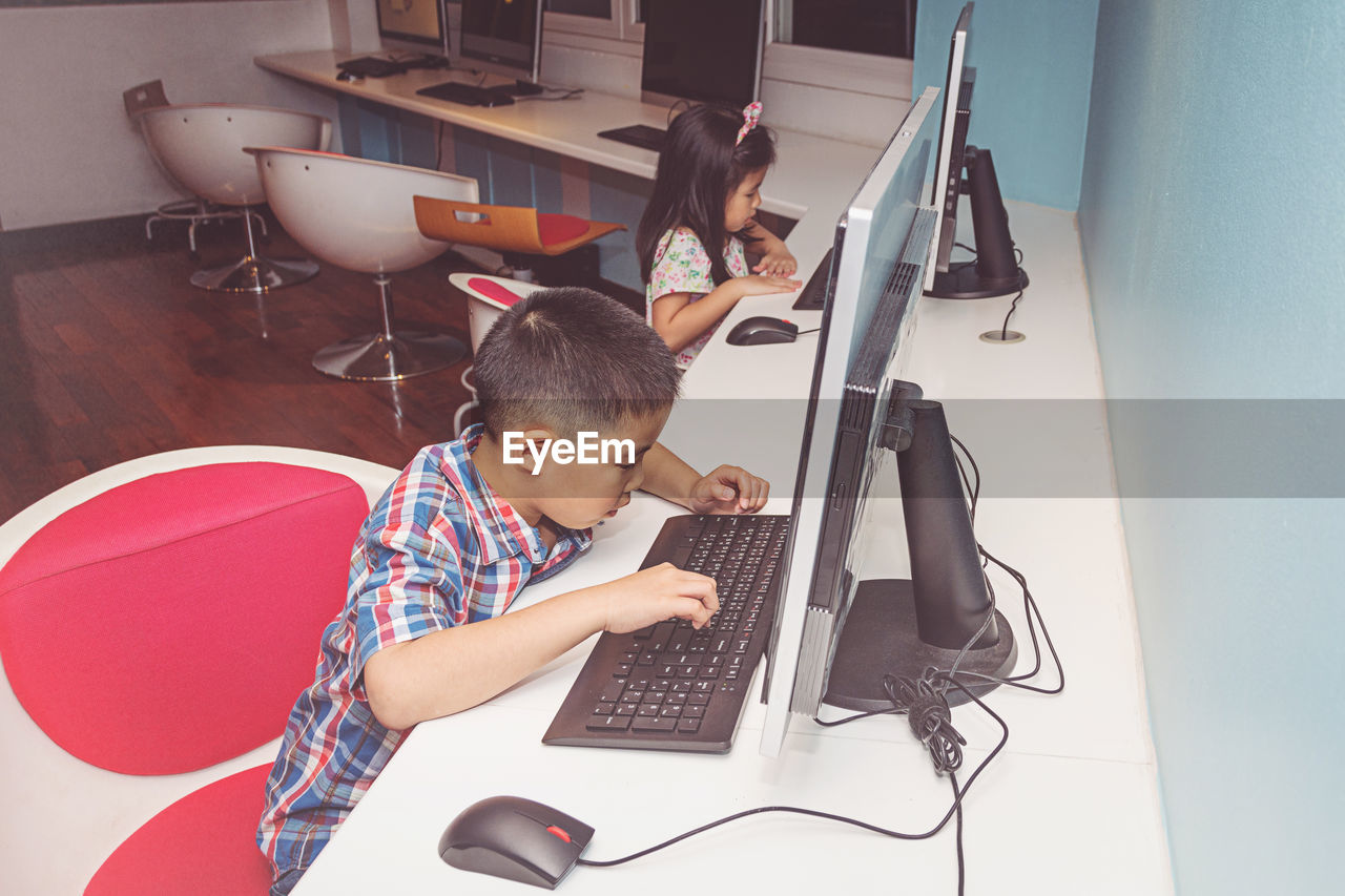 computer, technology, males, child, real people, men, laptop, childhood, indoors, wireless technology, boys, connection, one person, casual clothing, home interior, sitting, communication, leisure activity, keyboard, using laptop, innocence