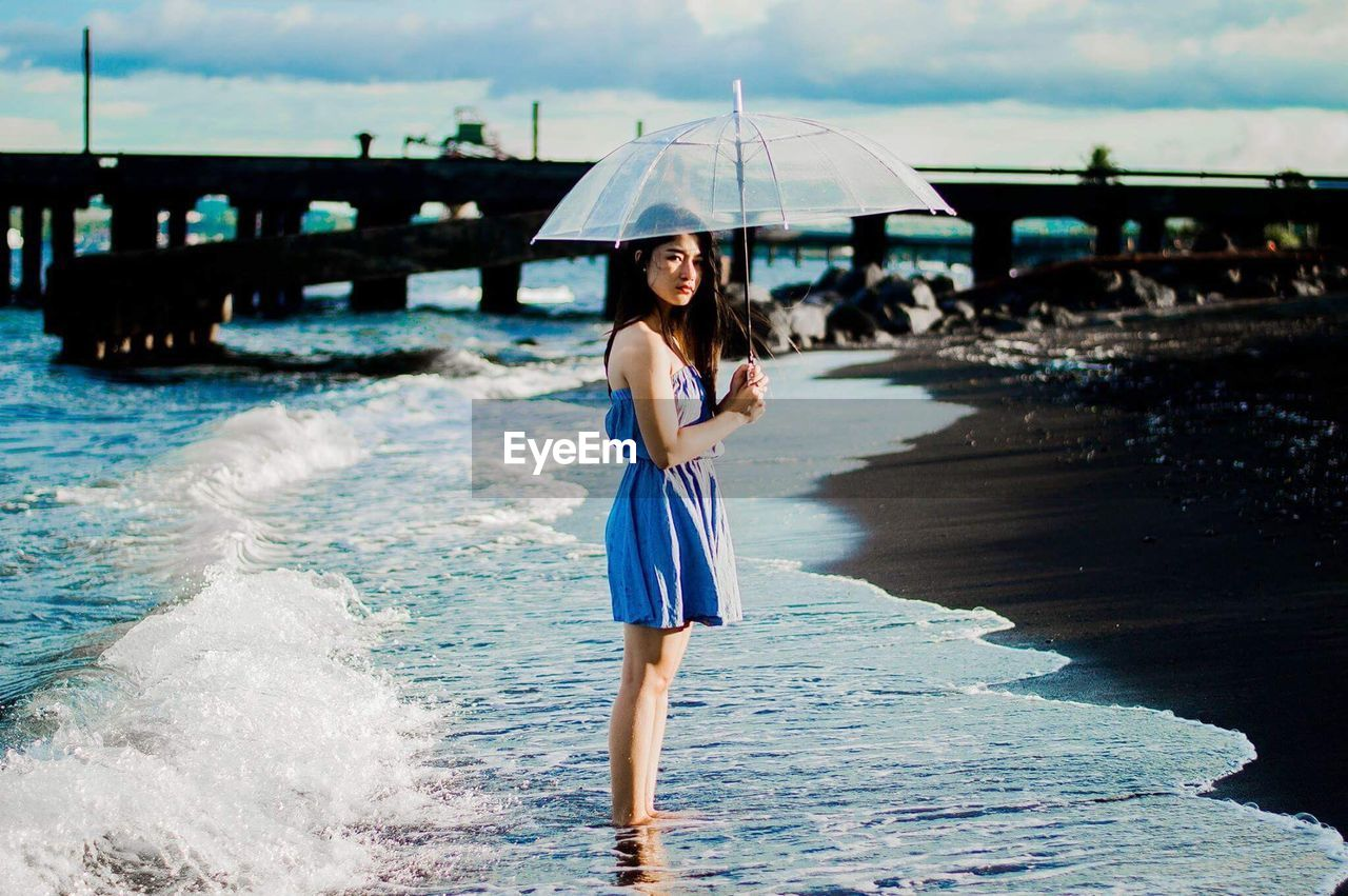 water, one person, beach, real people, looking at camera, beautiful woman, young adult, portrait, happiness, sea, outdoors, leisure activity, front view, lifestyles, beauty, full length, day, sand, smiling, vacations, young women, standing, nature, ankle deep in water, wave, beauty in nature, adult, people