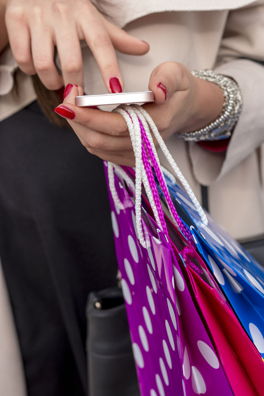 Midsection of woman holding shopping bags using mobile phone
