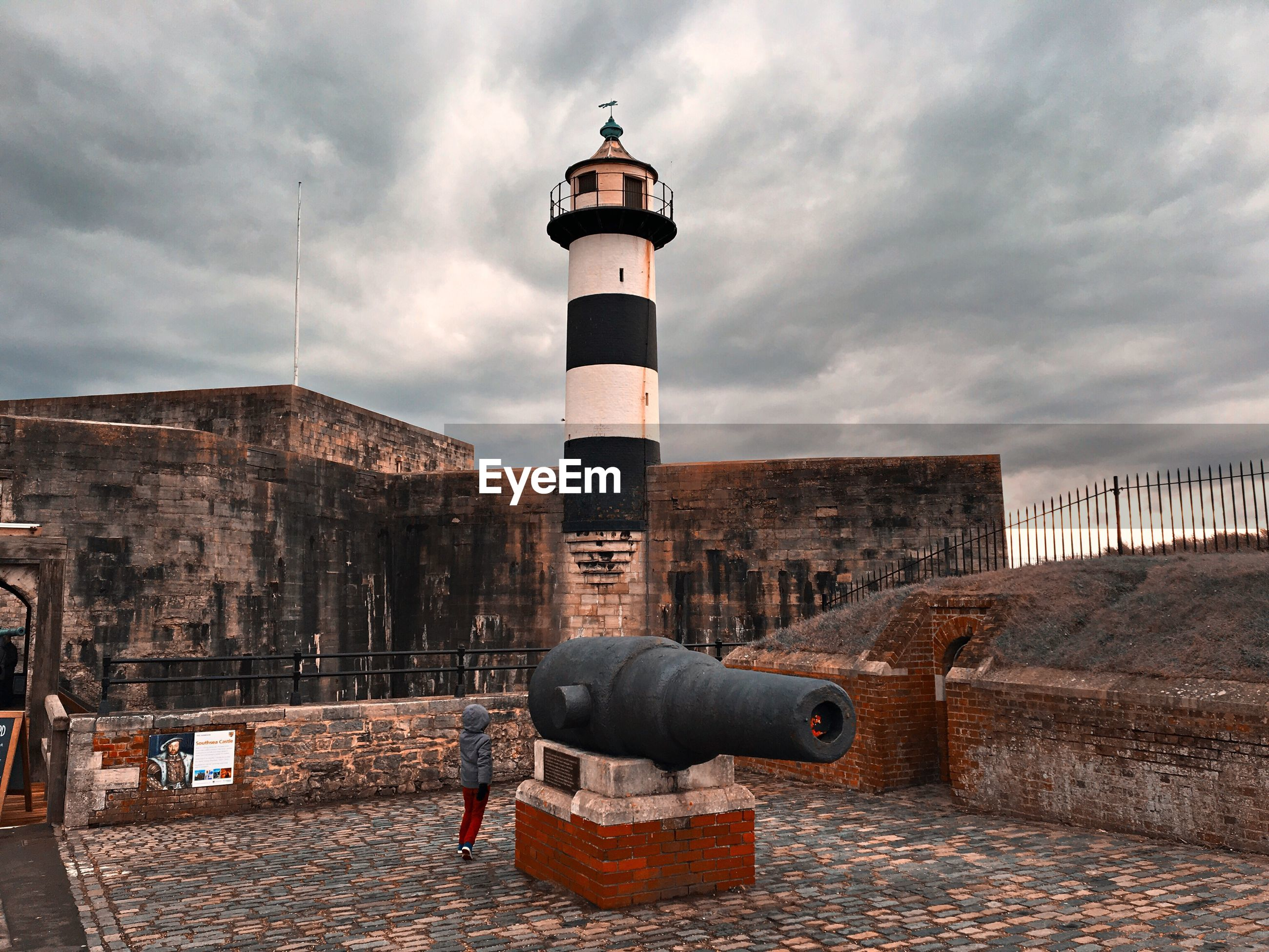 Rear view of boy by cannon against cloudy sky at southsea castle
