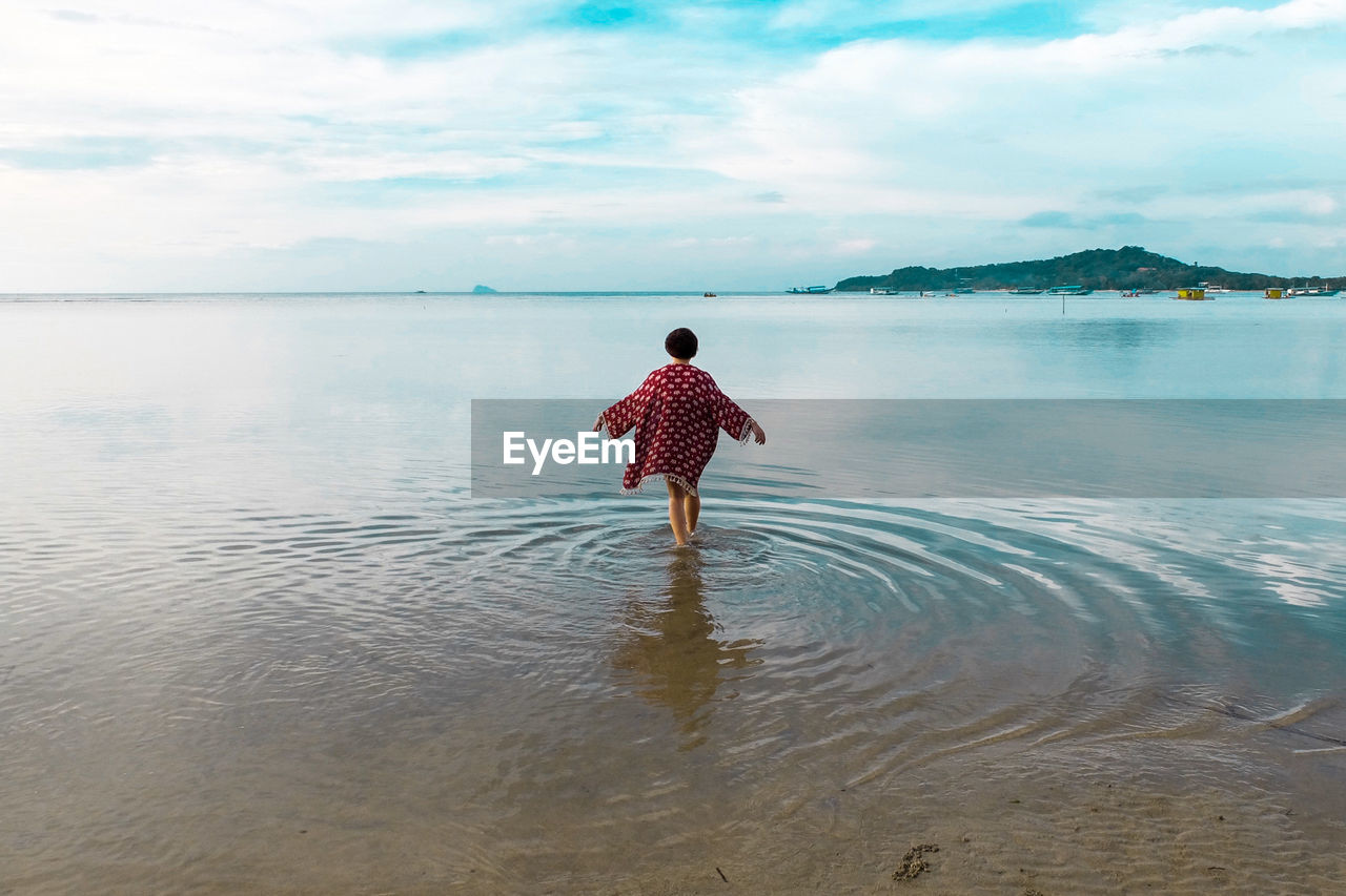 Rear View Of Woman Standing On Beach Against Cloudy Sky