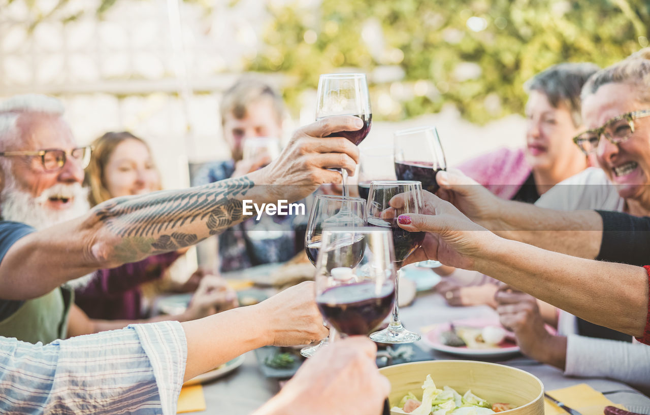 group of people, men, celebratory toast, women, glass, togetherness, alcohol, mature men, refreshment, adult, real people, holding, medium group of people, friendship, smiling, food and drink, mature adult, wineglass, wine, males, hand, social gathering