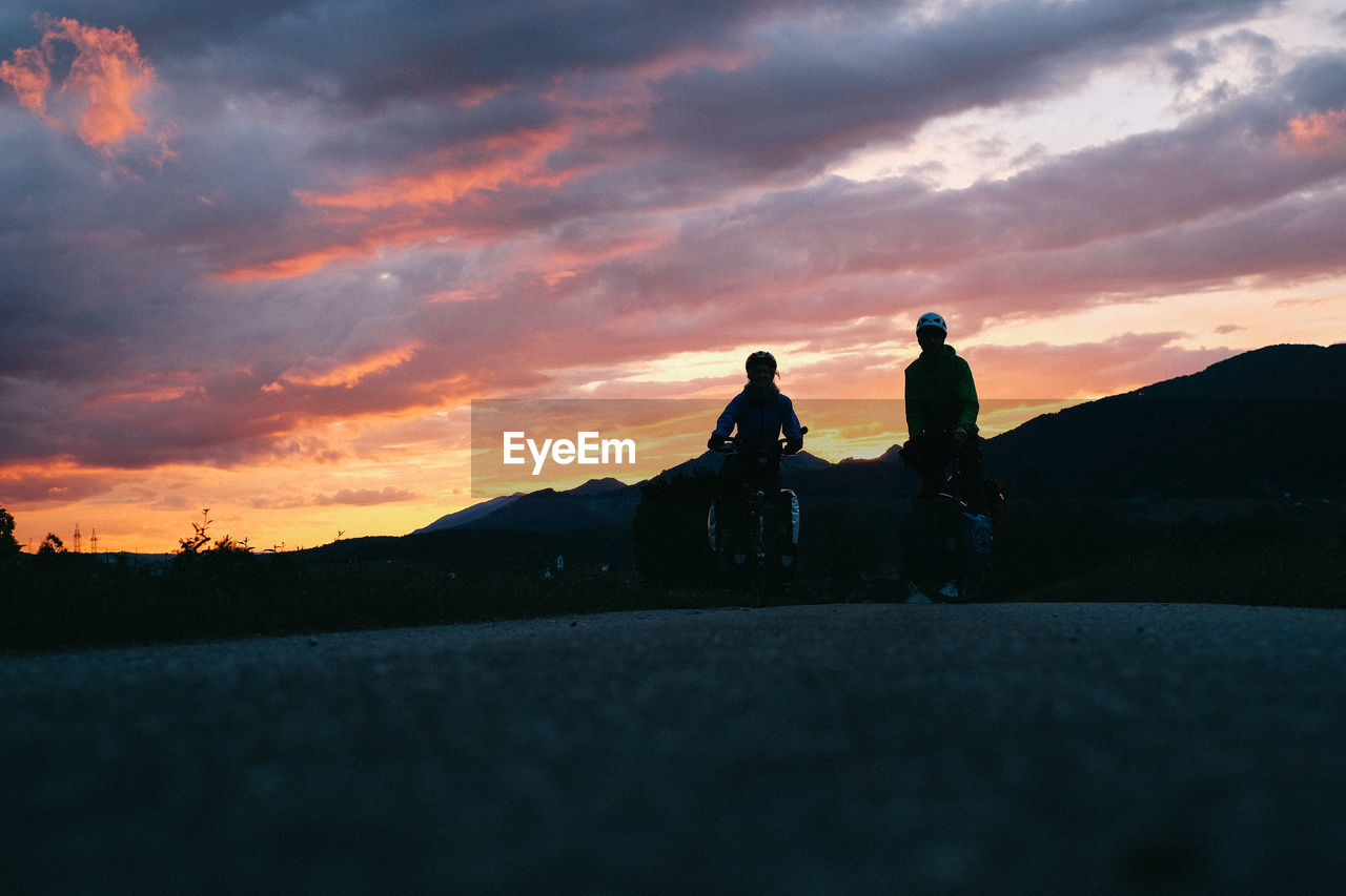 Man and woman with bicycle on field against cloudy sky during sunset