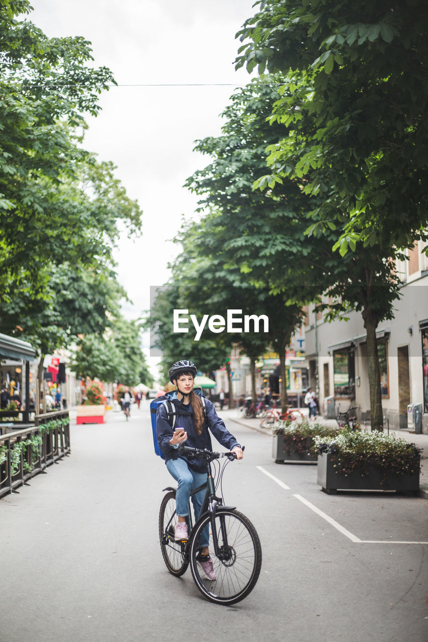 MAN RIDING BICYCLE ON CITY STREET IN PARK