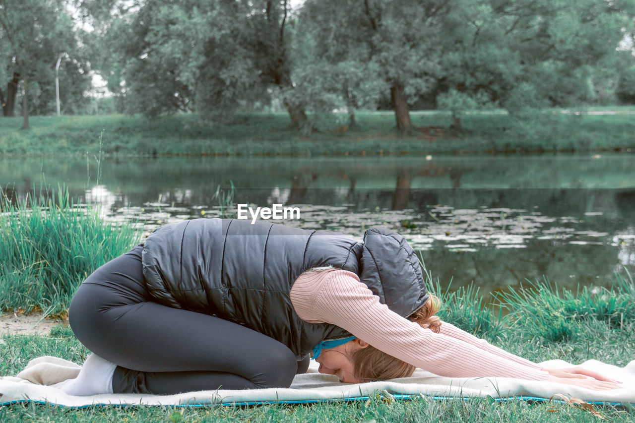 Young woman practicing yoga in the park. concept of mental health and wellness.