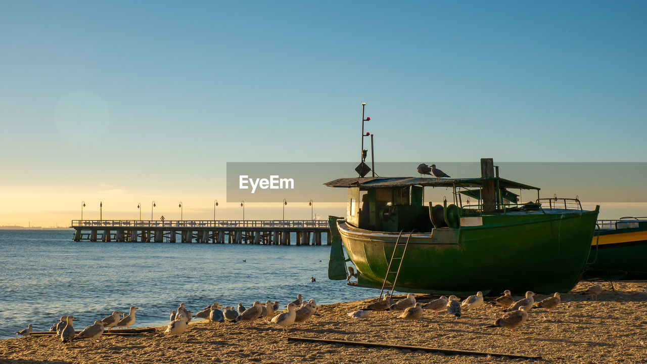 sky, water, nautical vessel, transportation, mode of transportation, sea, sunset, clear sky, nature, moored, copy space, no people, architecture, beach, pier, ship, scenics - nature, built structure, outdoors, fishing industry, cruise ship