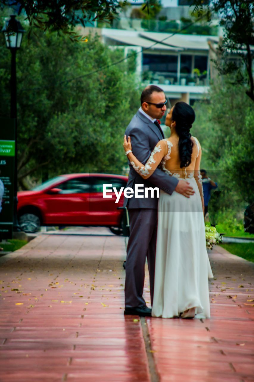love, togetherness, real people, bride, full length, wedding, two people, groom, bridegroom, couple - relationship, bonding, lifestyles, young women, wedding dress, standing, women, life events, celebration, day, men, young adult, outdoors, well-dressed, tree