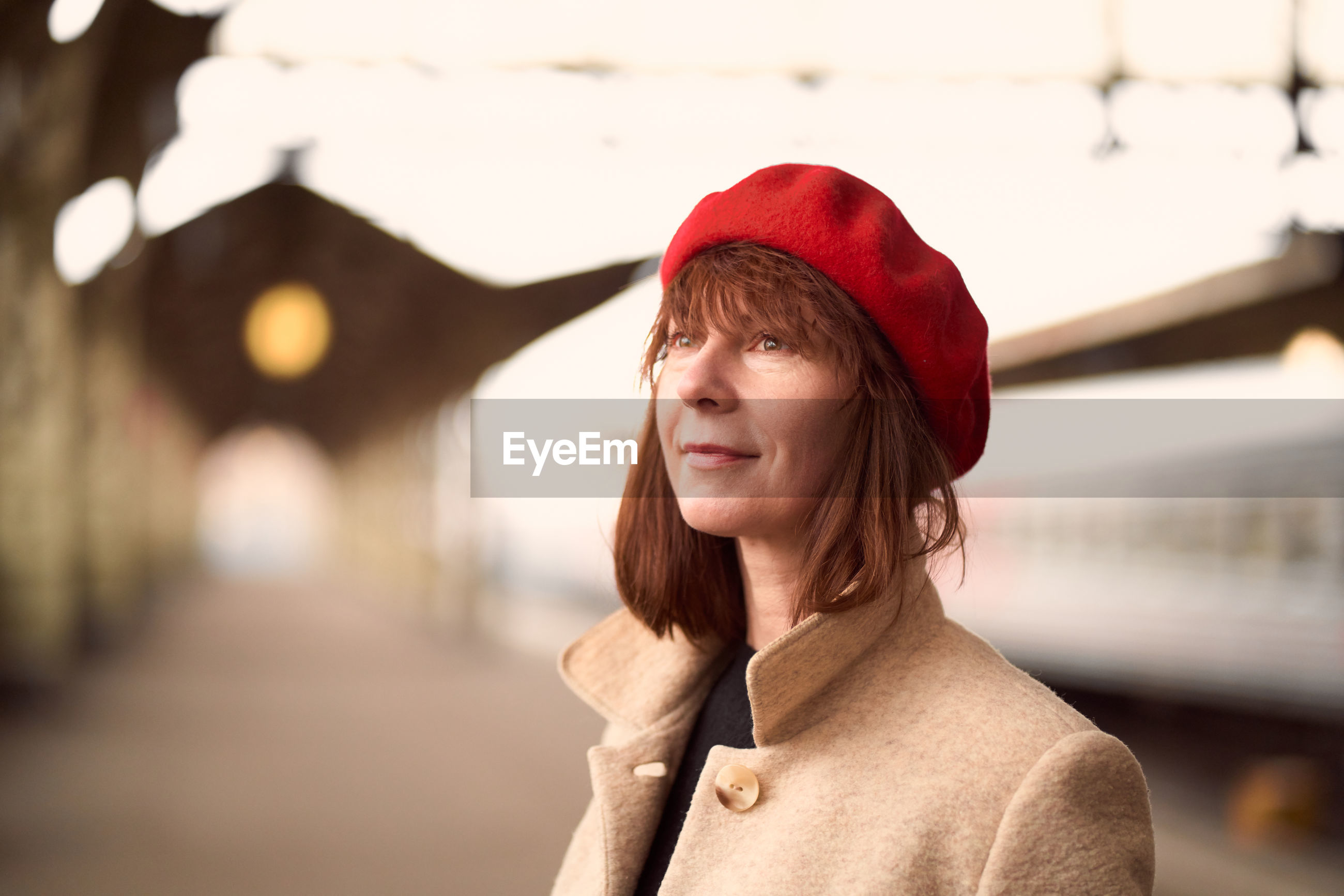 Smiling woman standing on railroad station