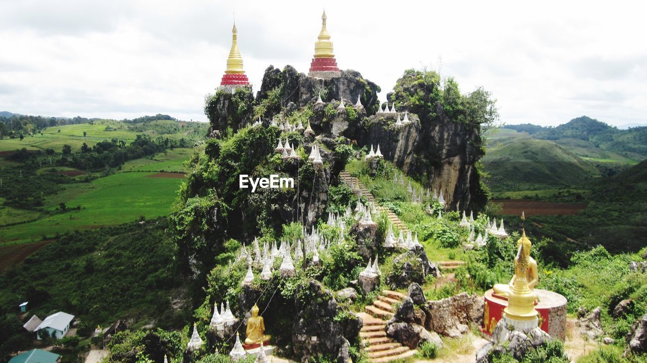 Stupas on cliff against cloudy sky