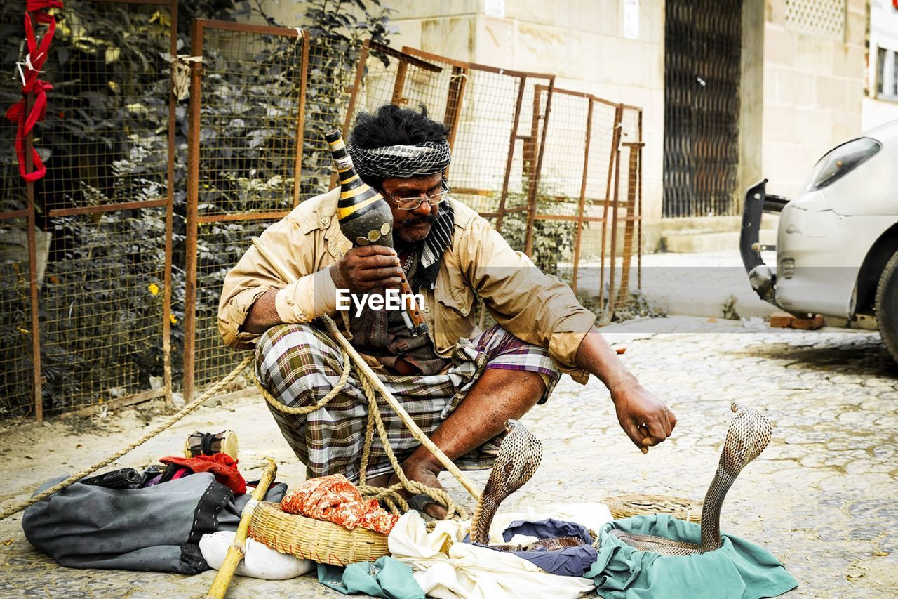 Indian snakecharmer playing flute on the street in mumbai, india.