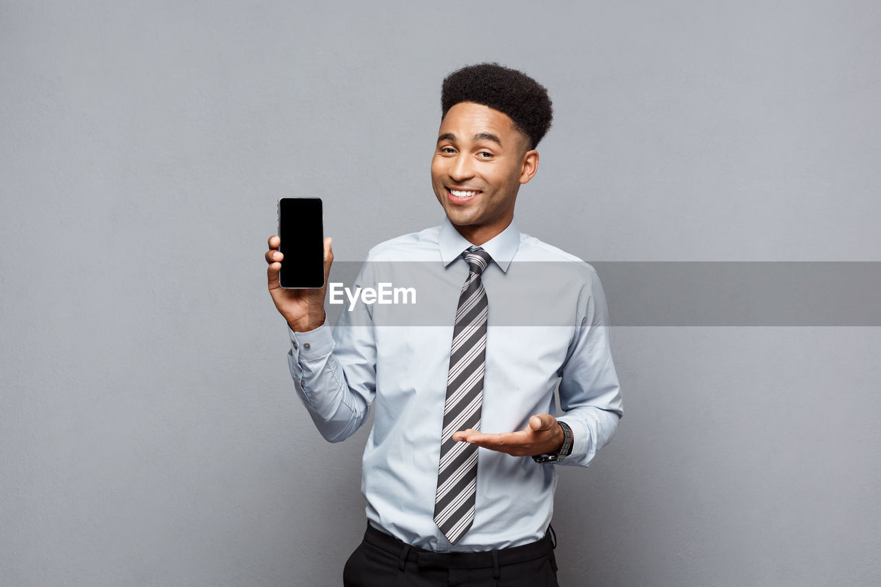 Portrait of businessman showing mobile phone screen while gesturing against gray background