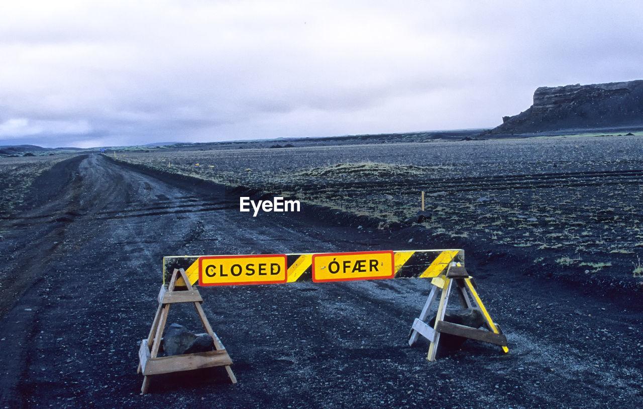Barricade On Dirt Road Against Sky