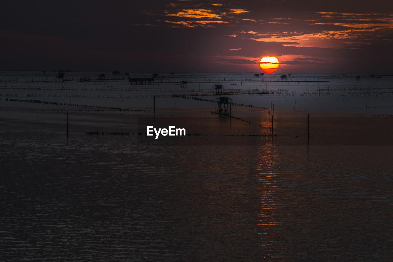sky, sunset, water, beauty in nature, scenics - nature, orange color, sea, tranquility, land, beach, idyllic, cloud - sky, sun, tranquil scene, nature, horizon over water, silhouette, non-urban scene, horizon, outdoors
