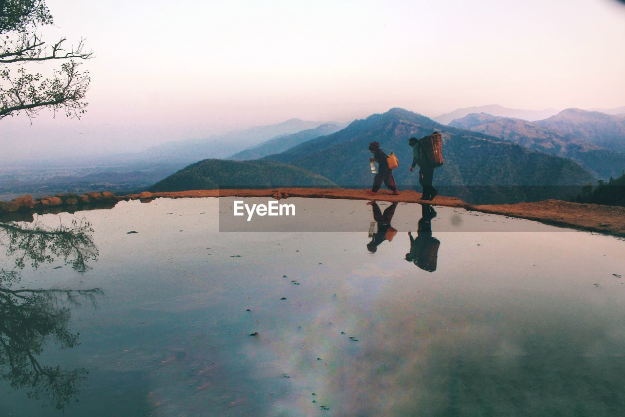 mountain, real people, nature, reflection, water, men, two people, leisure activity, scenics, lake, lifestyles, outdoors, beauty in nature, togetherness, day, mountain range, friendship, sky, vacations, adventure, women, full length, low section, people