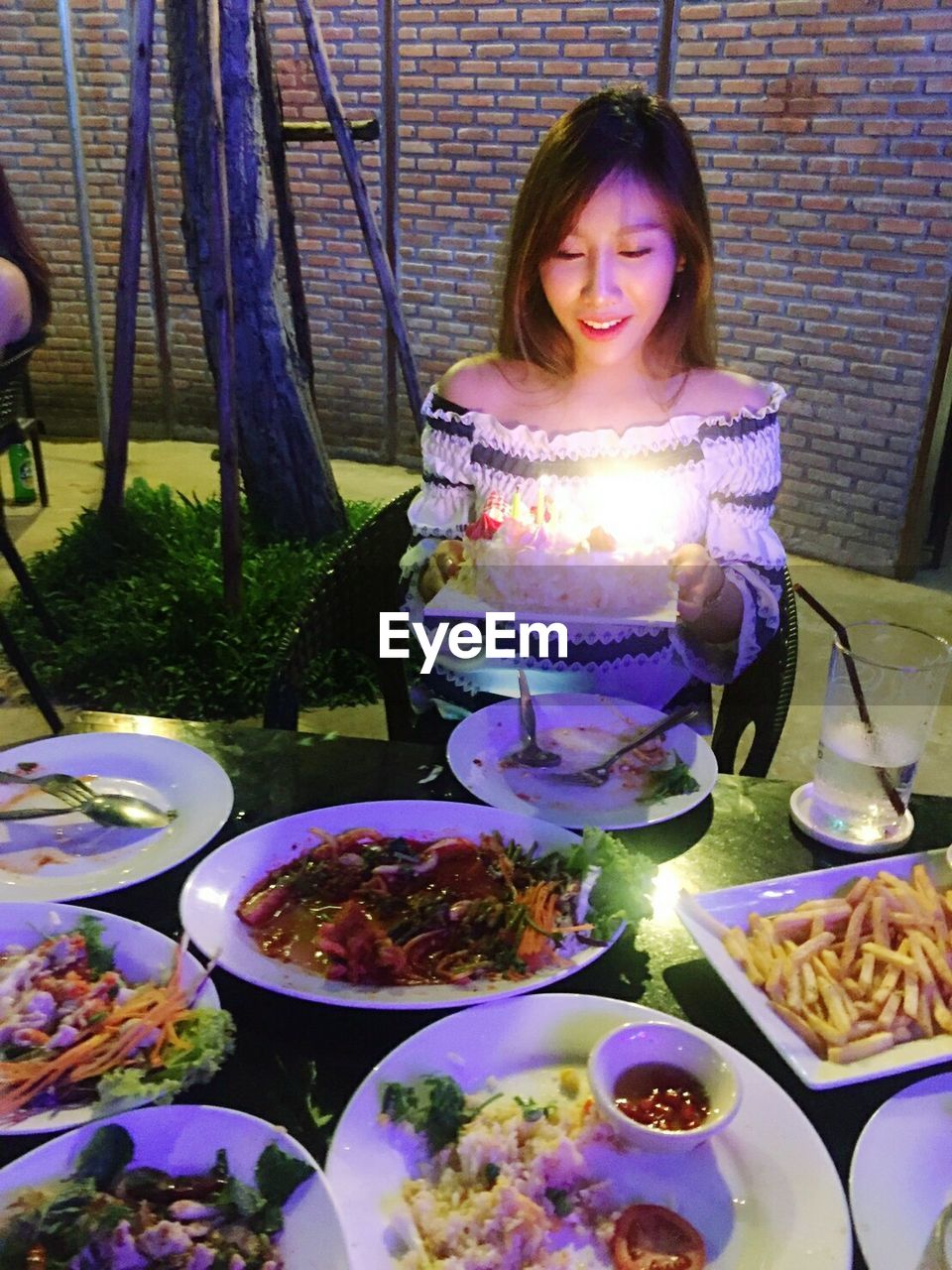 Woman Holding Birthday Cake With Various Food Served On Table
