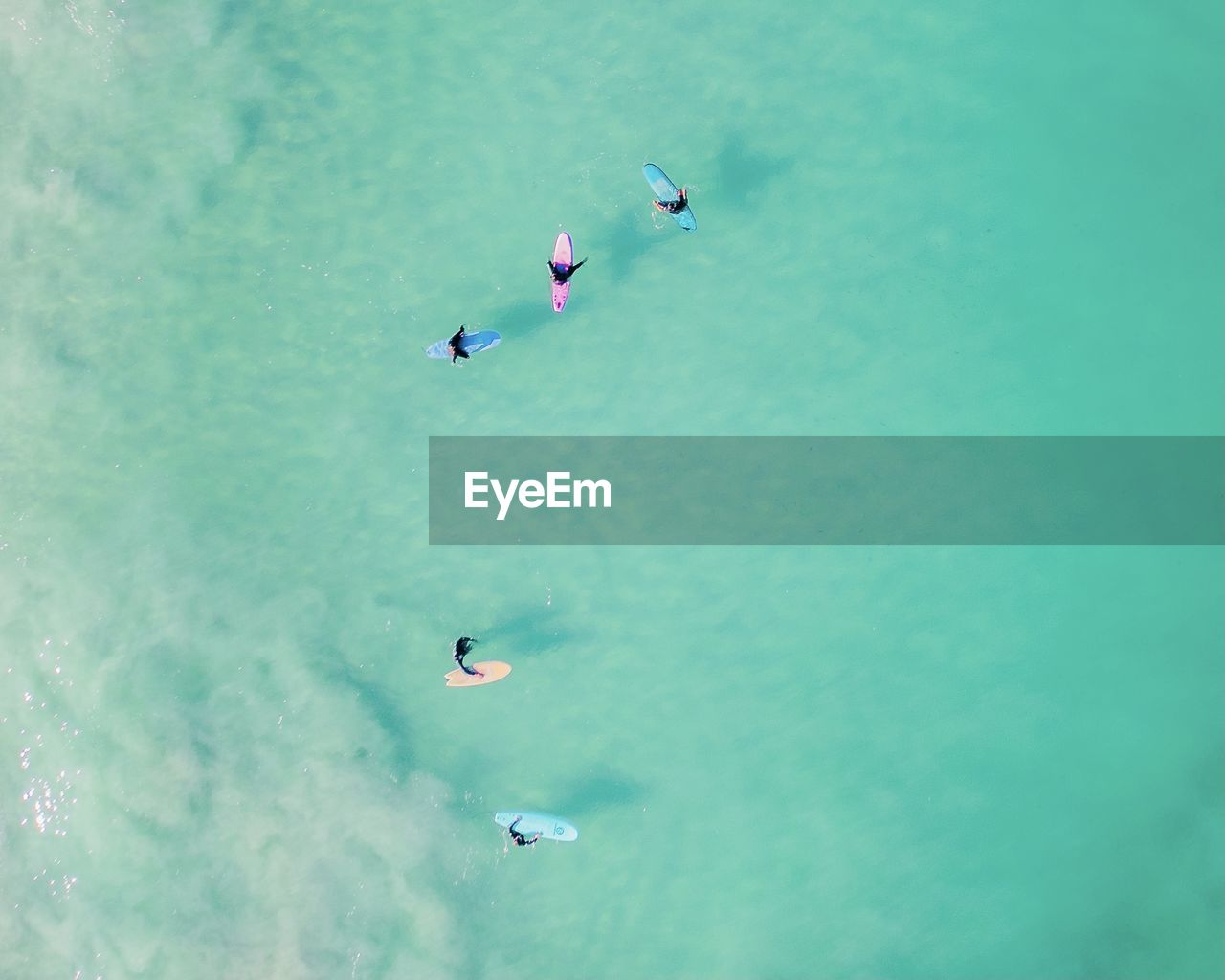 HIGH ANGLE VIEW OF PEOPLE FLYING IN SEA