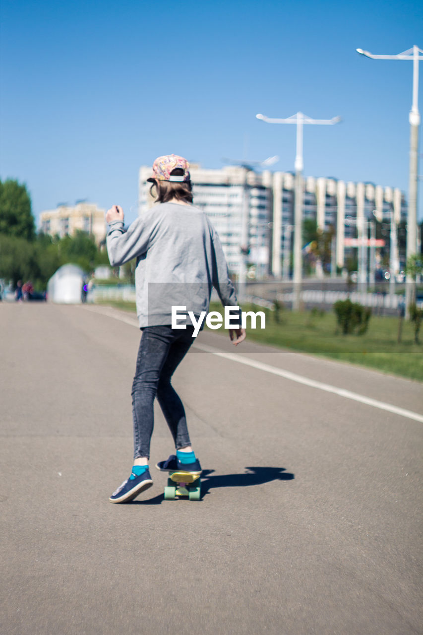 full length, one person, leisure activity, casual clothing, real people, road, day, sports equipment, lifestyles, city, skateboard, transportation, sky, sunlight, motion, focus on foreground, nature, sport, outdoors, human arm