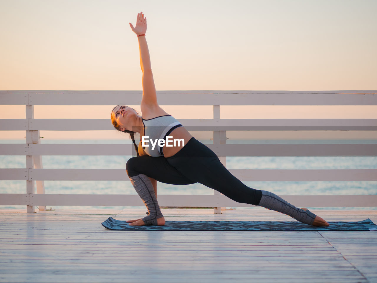Full Length Of Woman Doing Yoga On Promenade Against Clear Sky During Sunrise