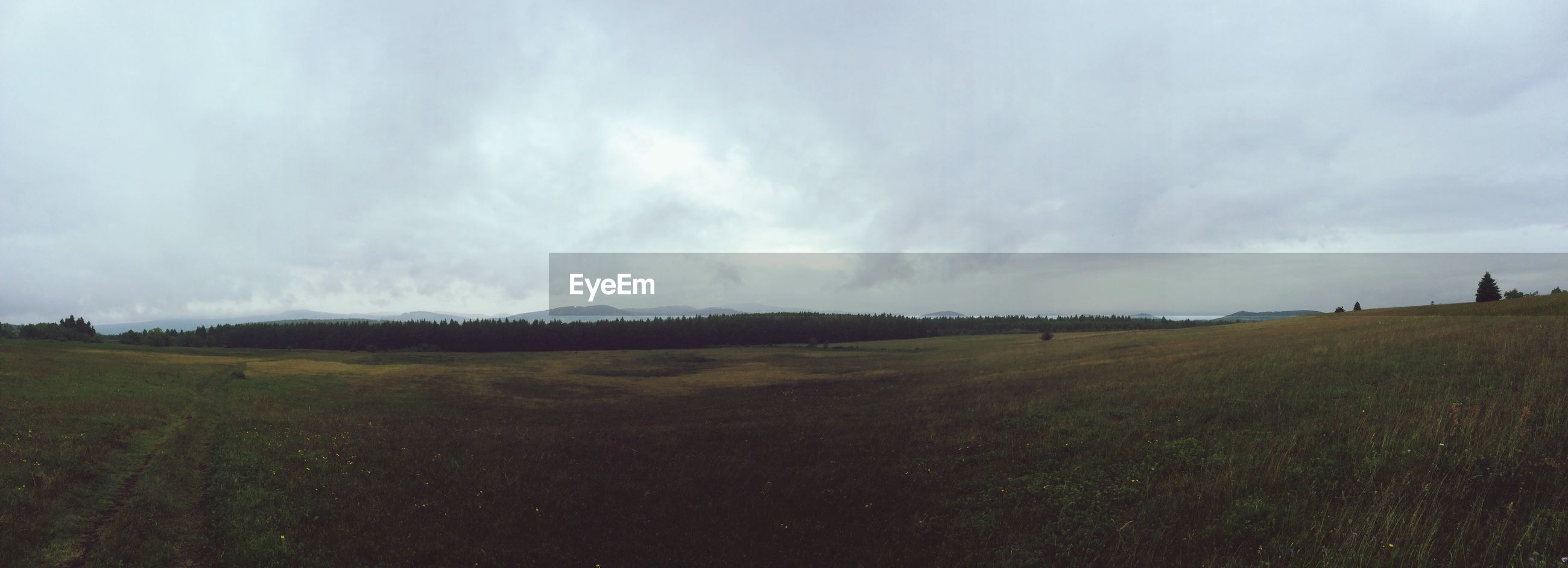 Panoramic shot of countryside landscape against sky and clouds