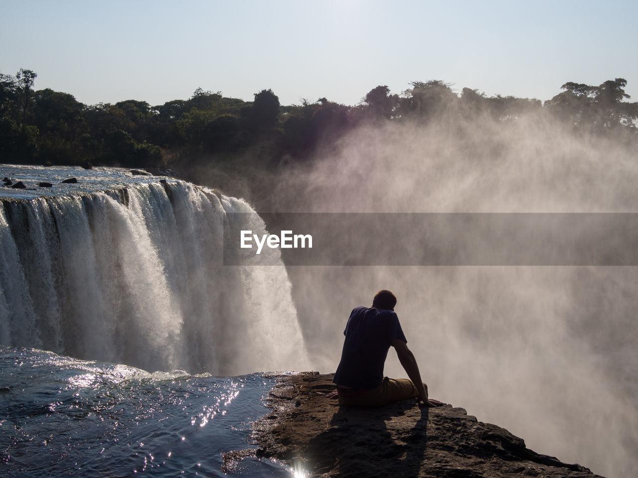 Rear View Of Man Sitting At Edge Of Lumangwe Waterfall, Zambia