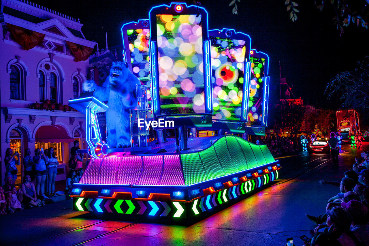 illuminated, night, multi colored, architecture, lighting equipment, neon, arts culture and entertainment, incidental people, city, representation, communication, nightlife, built structure, building exterior, outdoors, real people, light - natural phenomenon, amusement park, sign