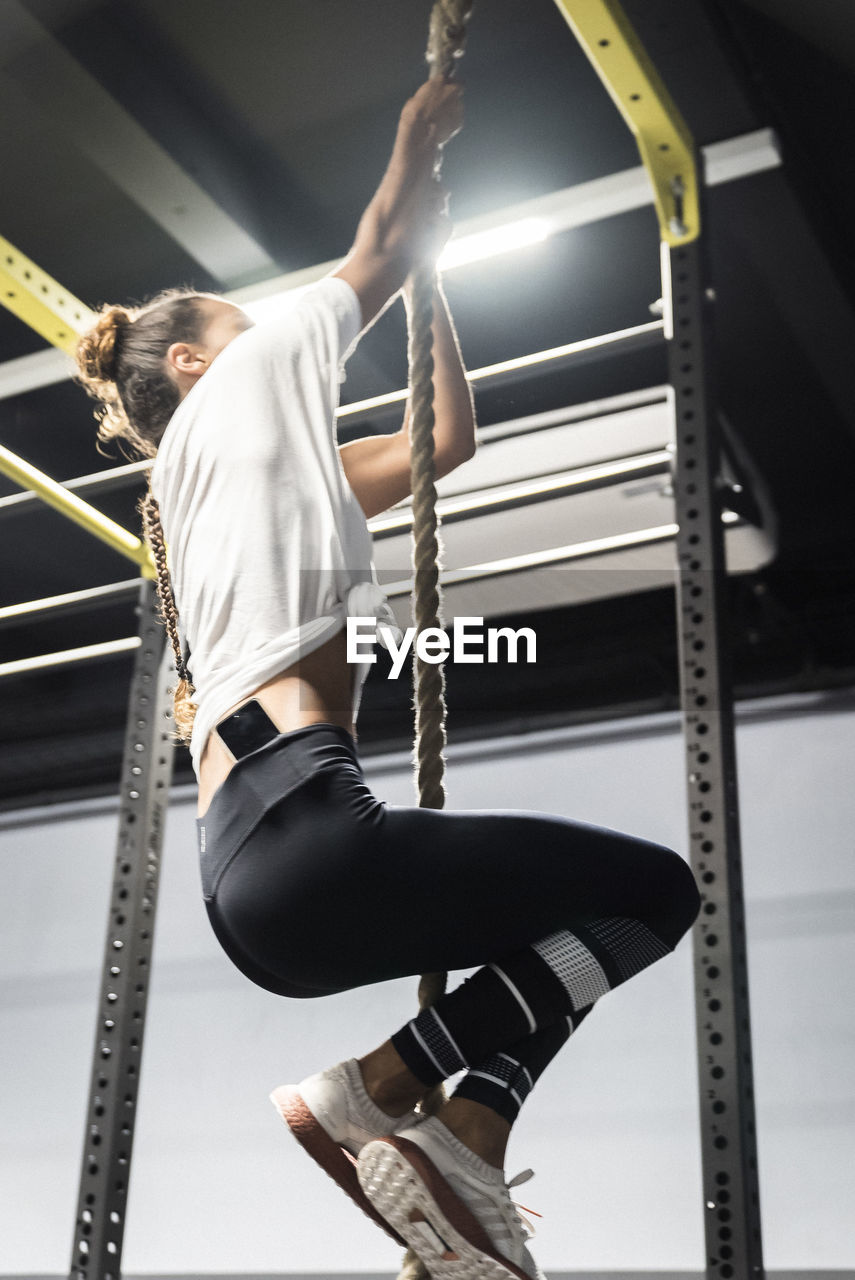 one person, real people, sport, lifestyles, strength, healthy lifestyle, exercising, vitality, climbing, three quarter length, young adult, sports clothing, balance, determination, focus on foreground, indoors, low angle view, skill, gym, hairstyle, effort, gymnastics, human arm, arms raised