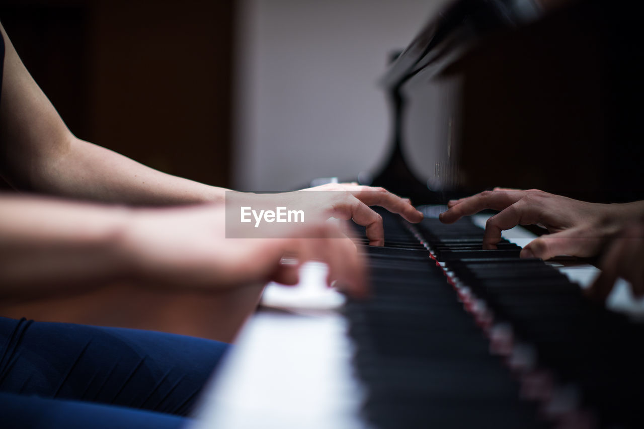 Cropped image of hands playing piano