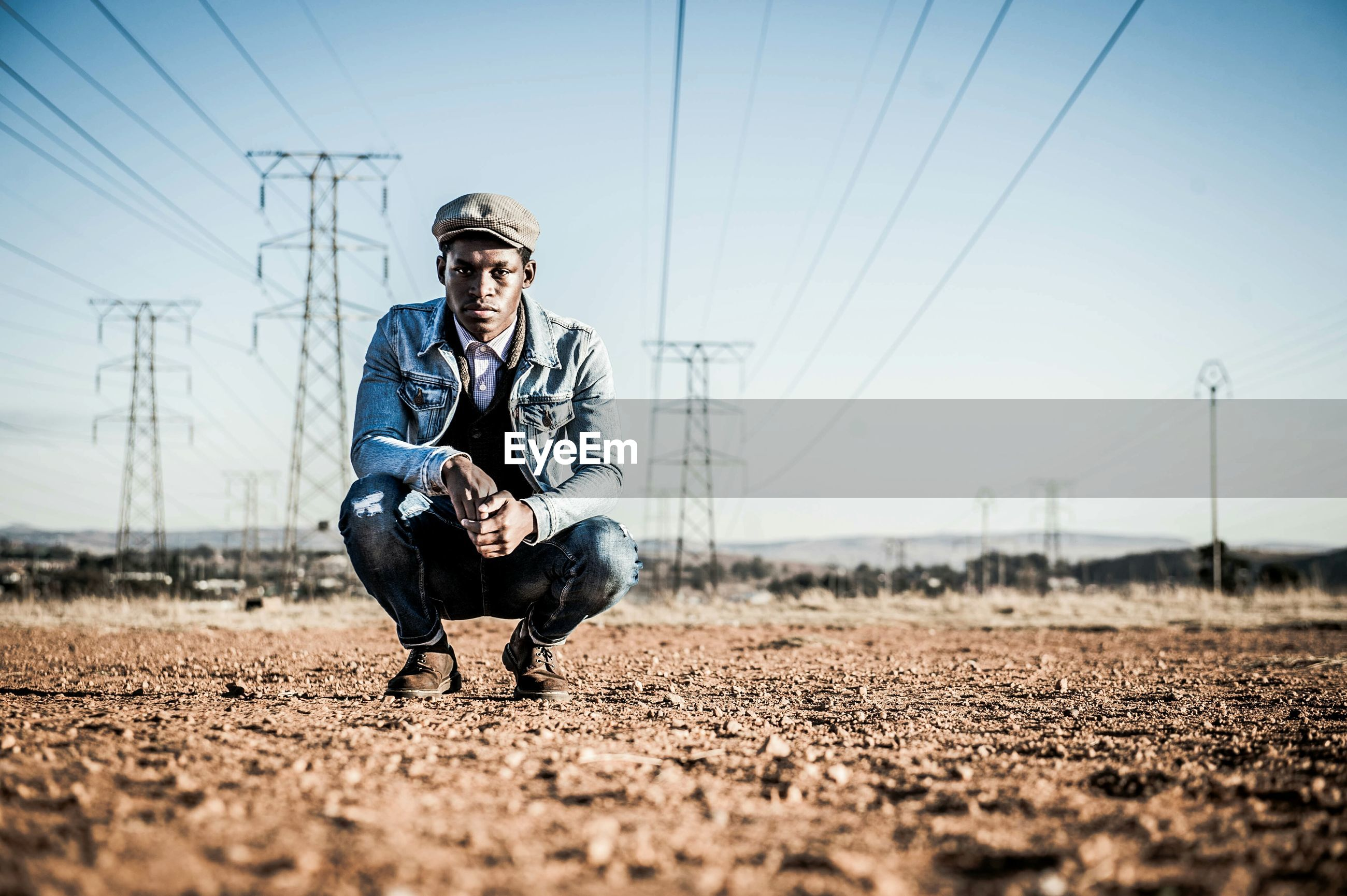 Portrait of man squatting under electricity pylons