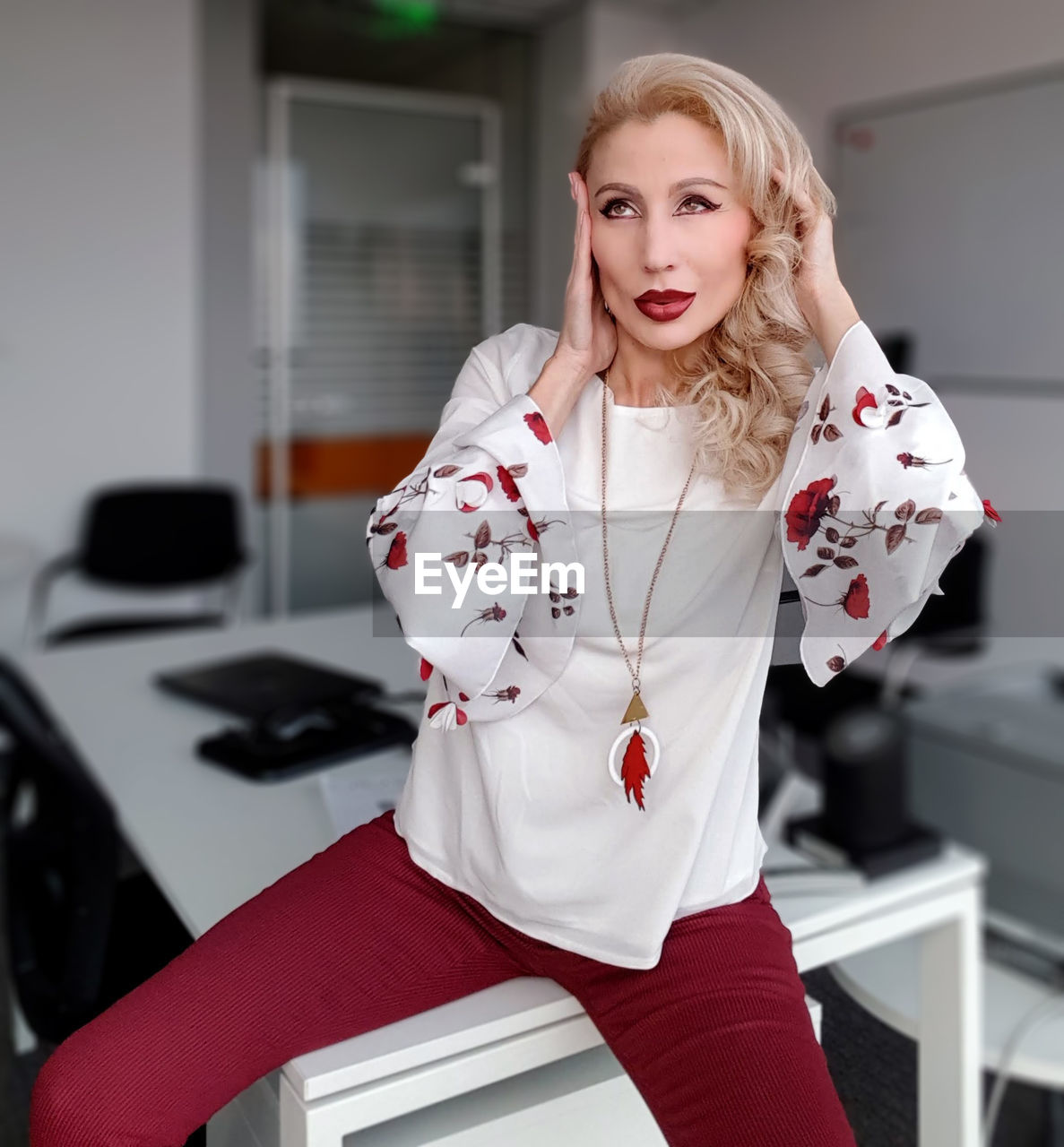 Beautiful woman looking away while sitting on table