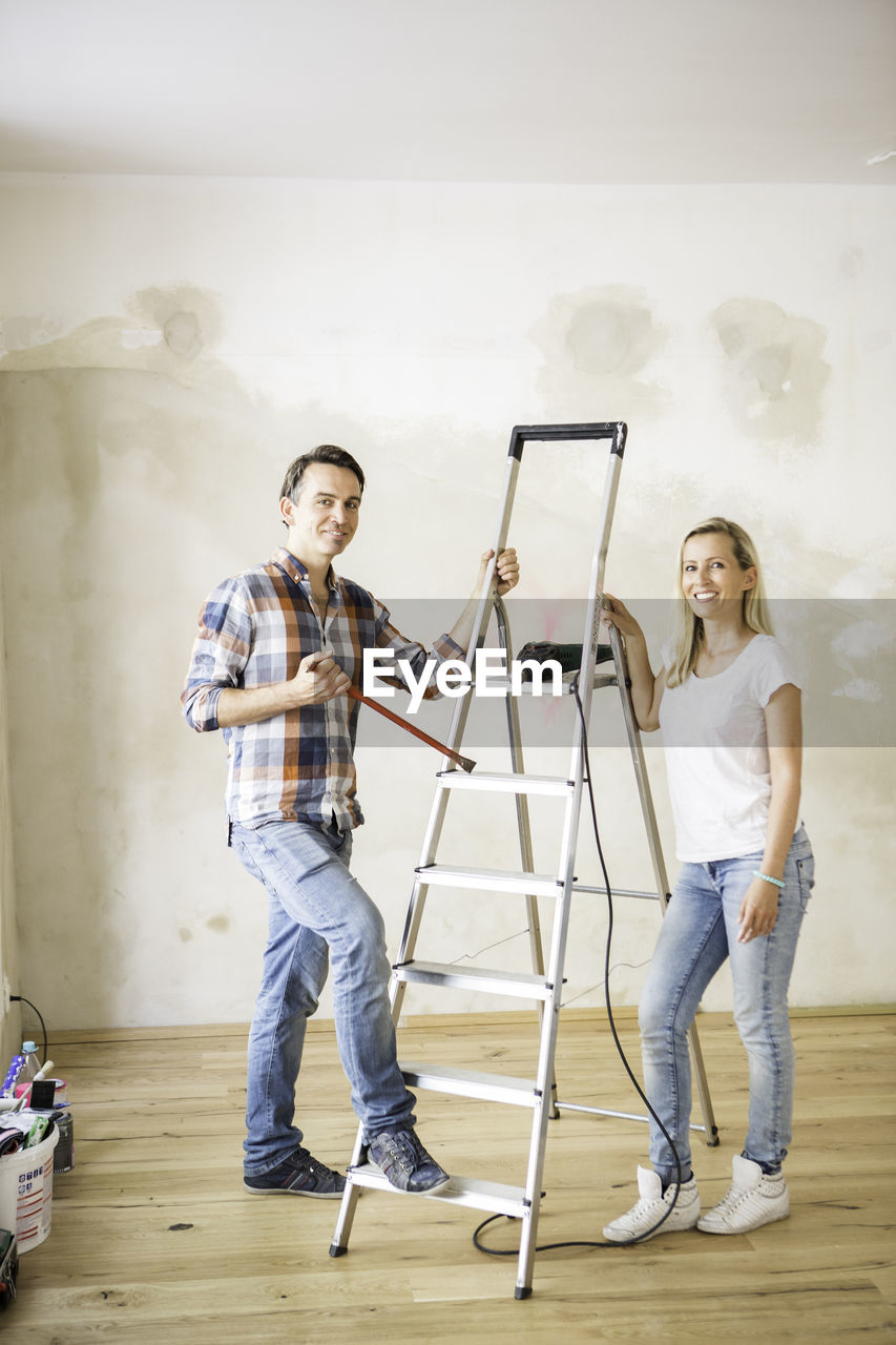 Portrait Of Young Couple Standing Amidst Ladder At Home During Renovation