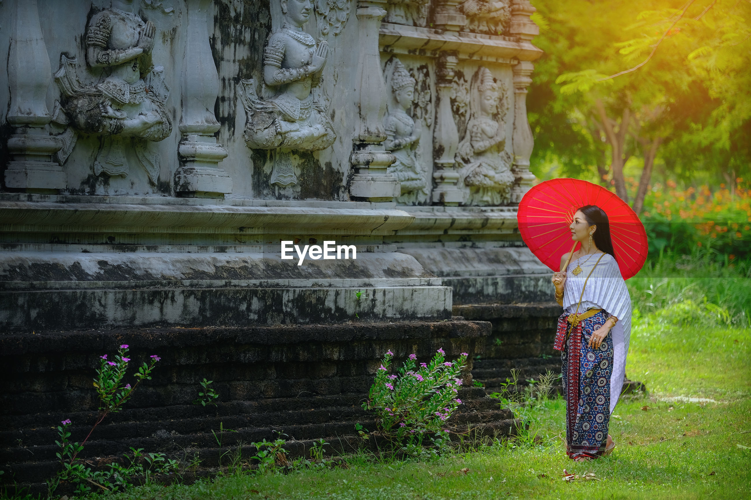 Woman with red umbrella standing by temple on grassy field