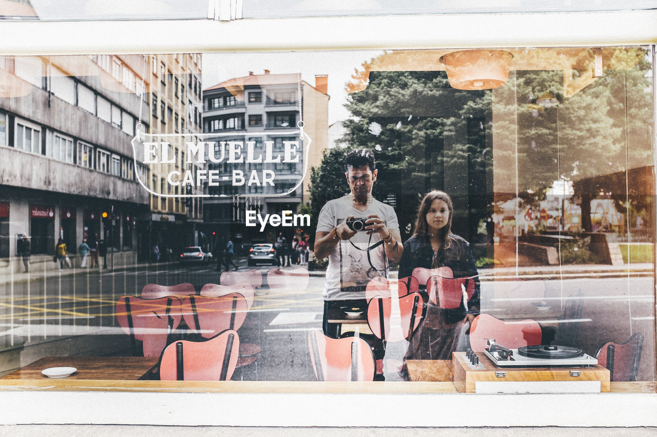 Man And Woman With Camera Reflecting On Glass Window Of Restaurant