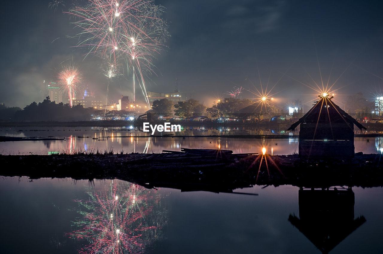 Firework display over illuminated city at night