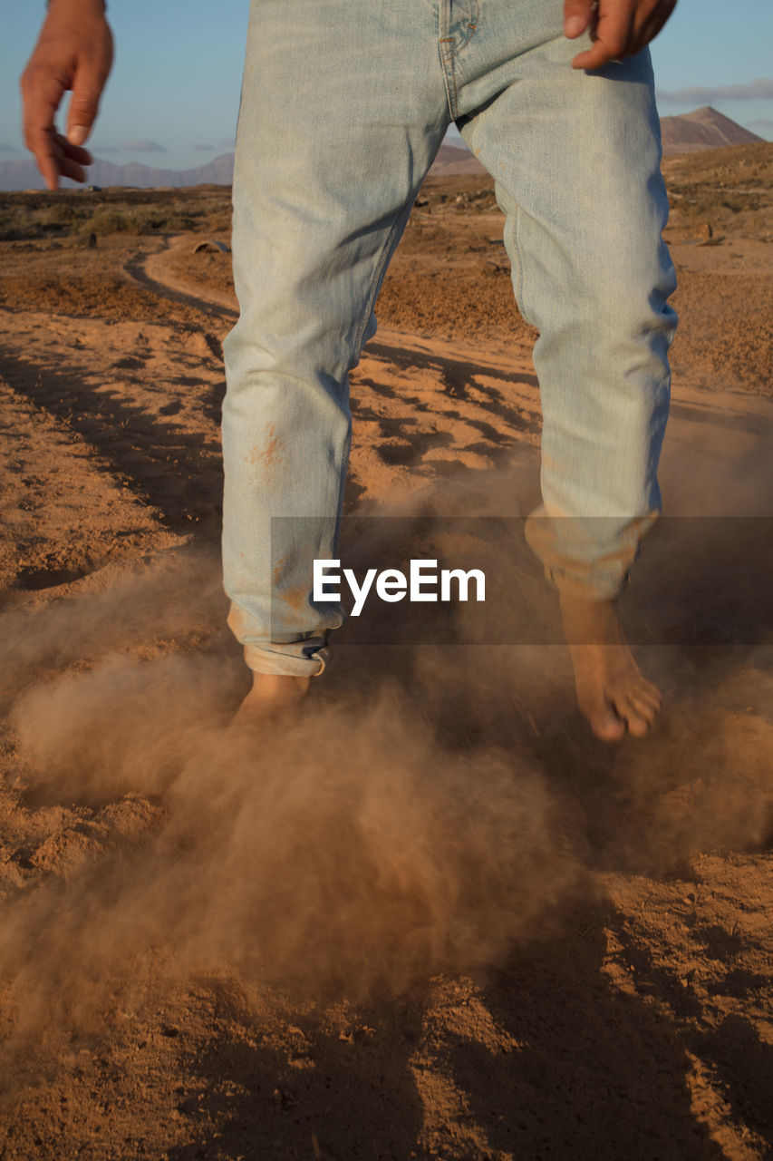 low section, human body part, human leg, land, real people, body part, one person, men, day, standing, nature, leisure activity, lifestyles, casual clothing, sand, outdoors, hand, dirt, sport, jeans, human limb, human foot
