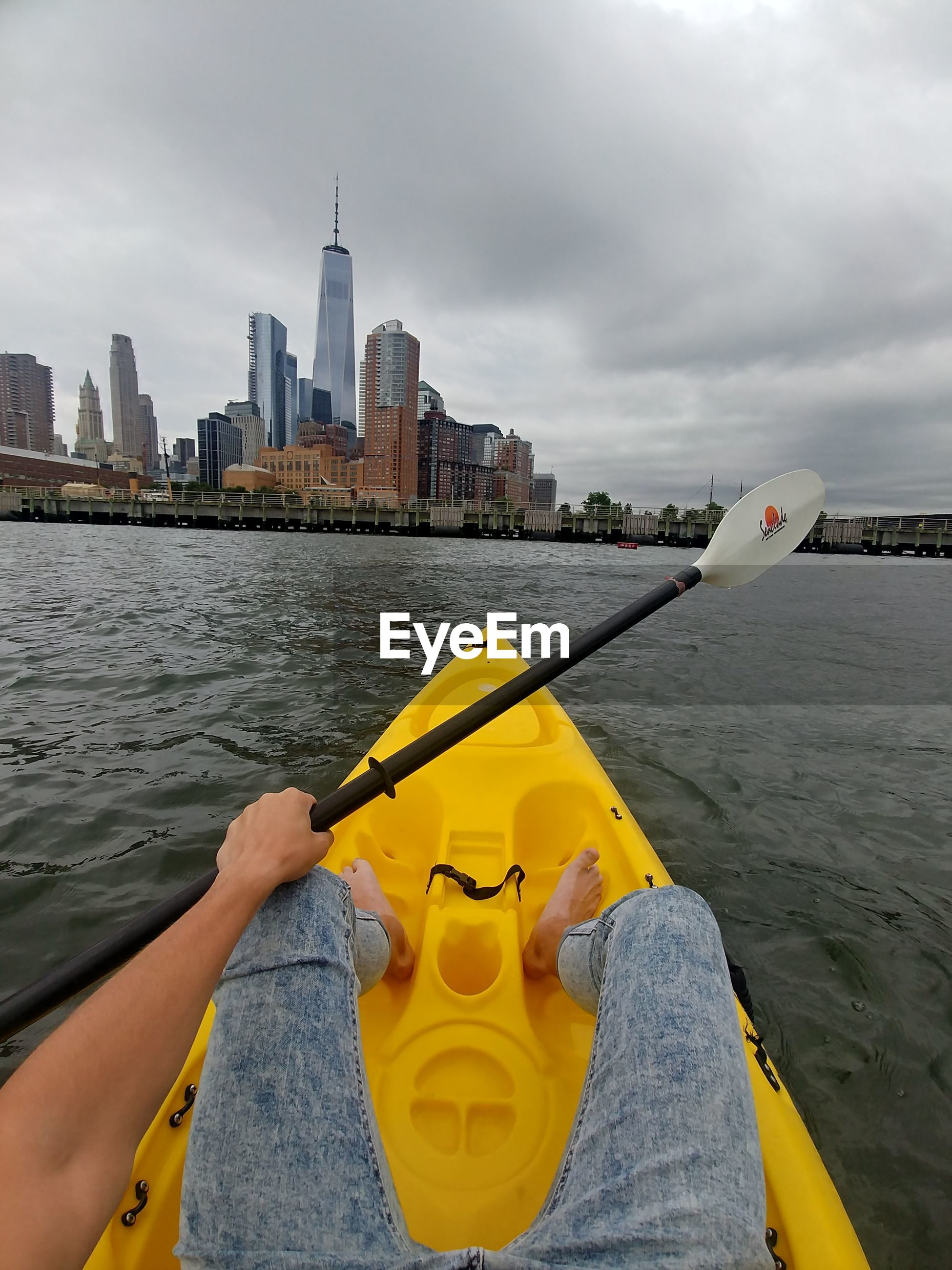 PERSON ON YELLOW BY RIVER AGAINST BUILDINGS IN CITY