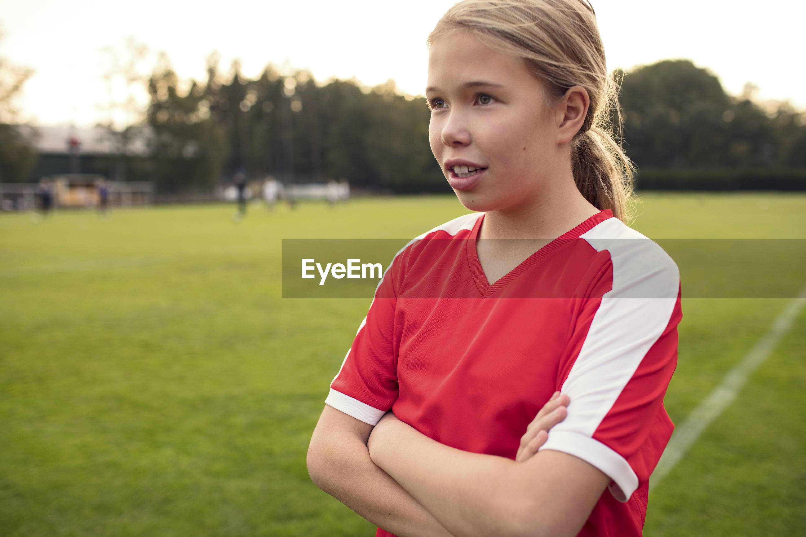PORTRAIT OF GIRL STANDING ON FIELD AT PARK