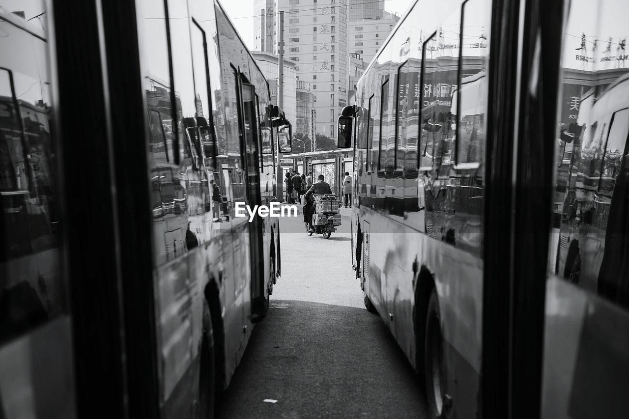 Man riding moped on street seen through buses