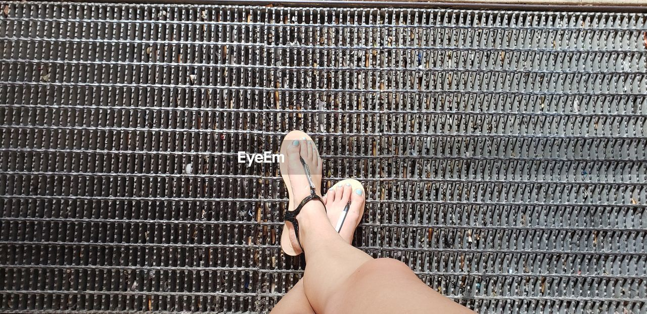 human body part, human hand, hand, real people, one person, body part, personal perspective, low section, lifestyles, pattern, metal, close-up, unrecognizable person, day, high angle view, barefoot, grate, metal grate, human leg, human foot, silver colored, finger