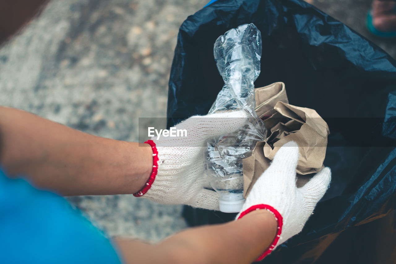 Cropped Hands Of Person Wearing Gloves Inserting Garbage In Plastic Bag
