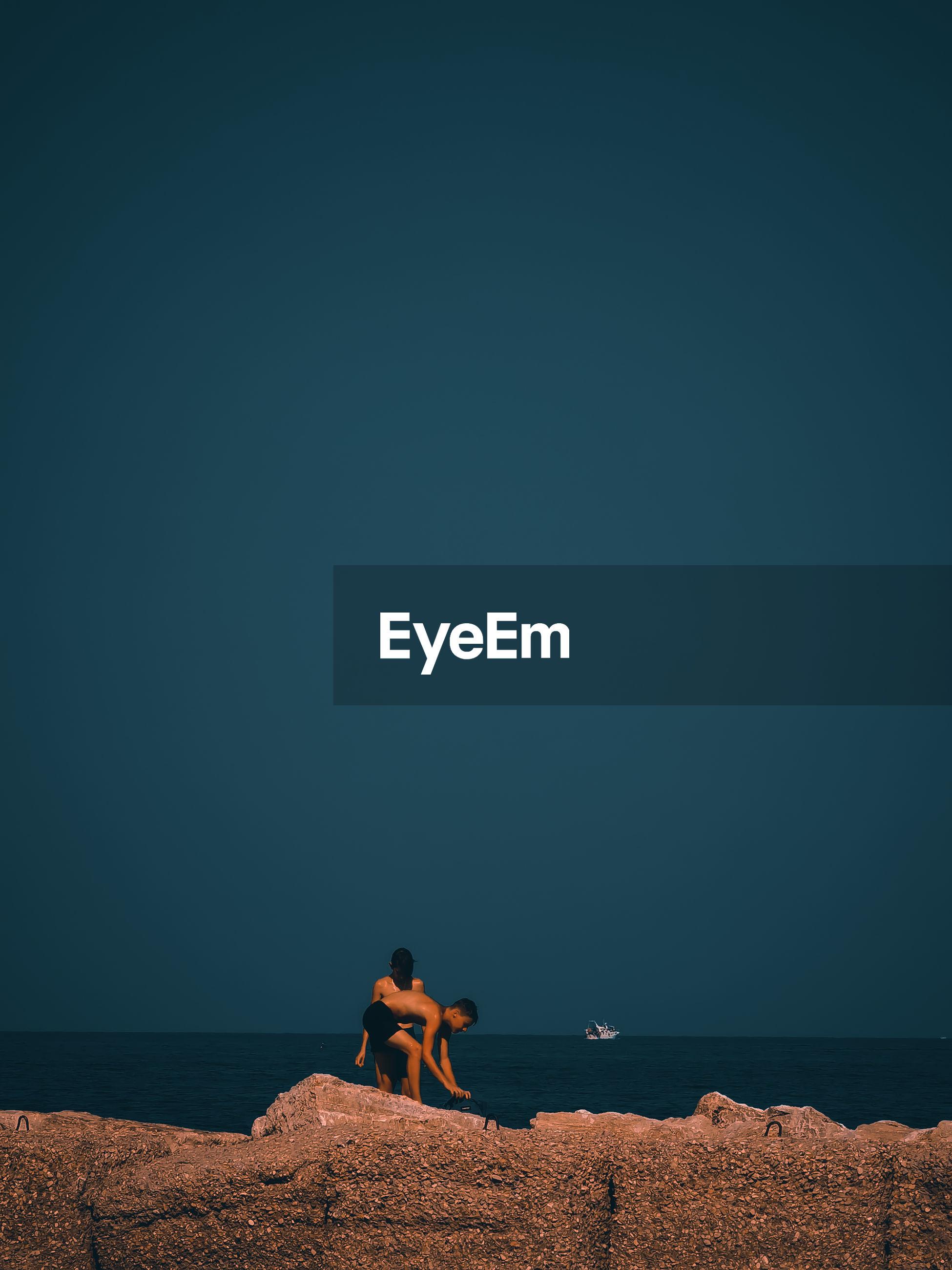 PEOPLE ON BEACH AGAINST SEA AGAINST SKY