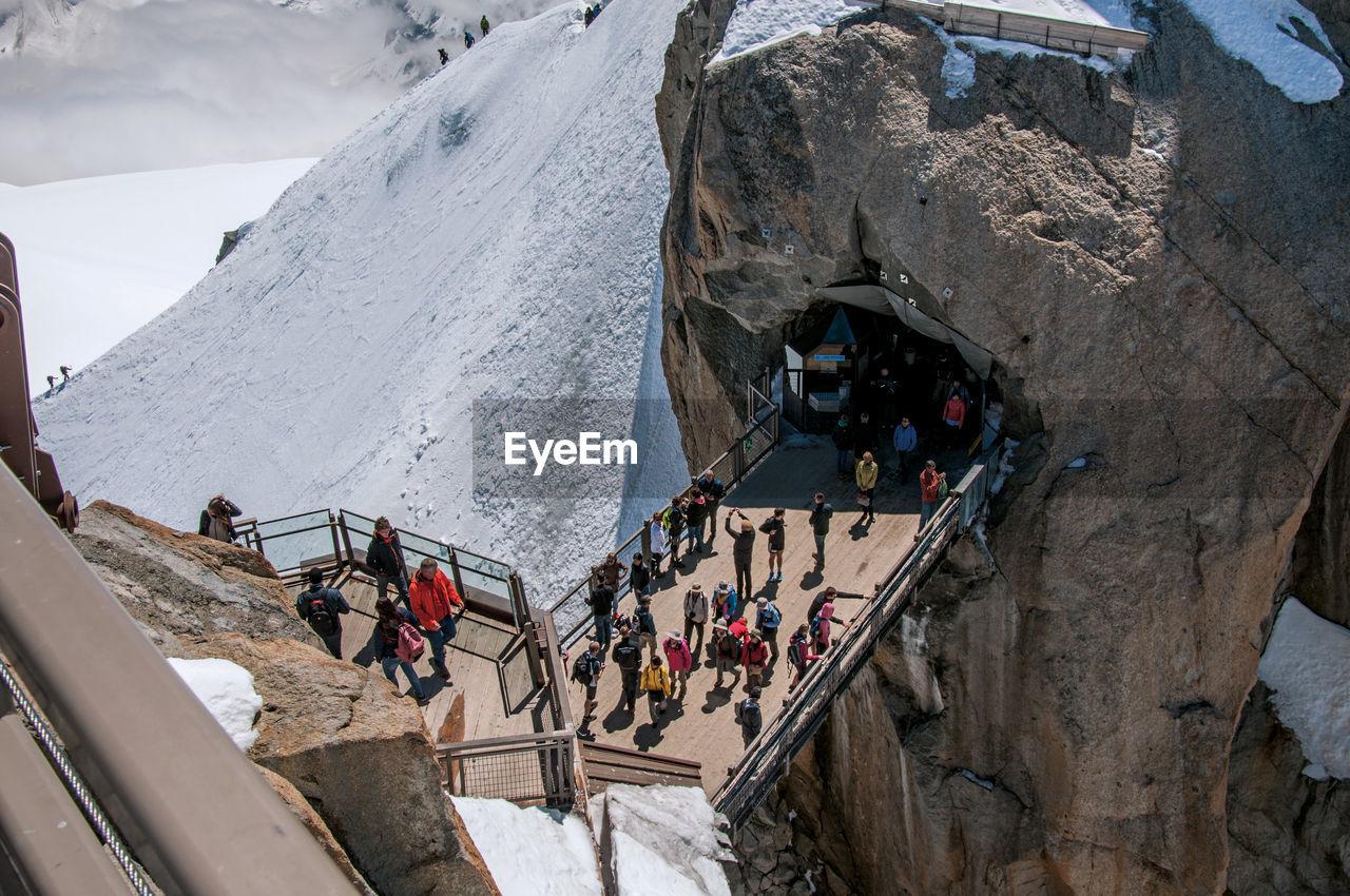 Footbridge between rocky peaks with tourists on the aiguille du midi, near chamonix, france.