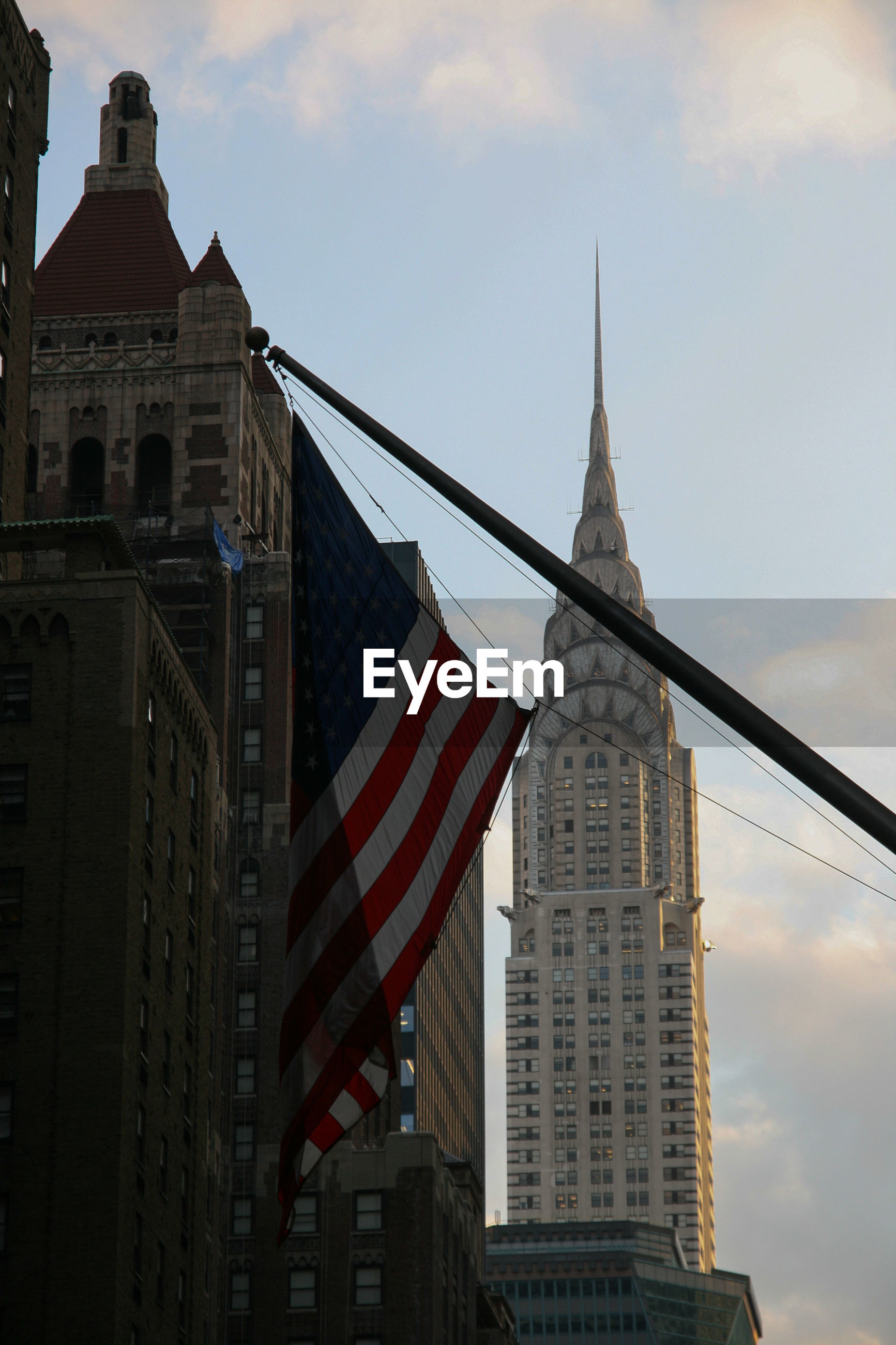 Low angle view of american flag in front of chrysler building