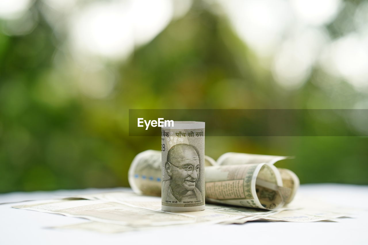currency, wealth, table, finance, no people, still life, close-up, business, focus on foreground, coin, selective focus, savings, day, representation, paper, green color, creativity, finance and economy, investment, human representation, economy