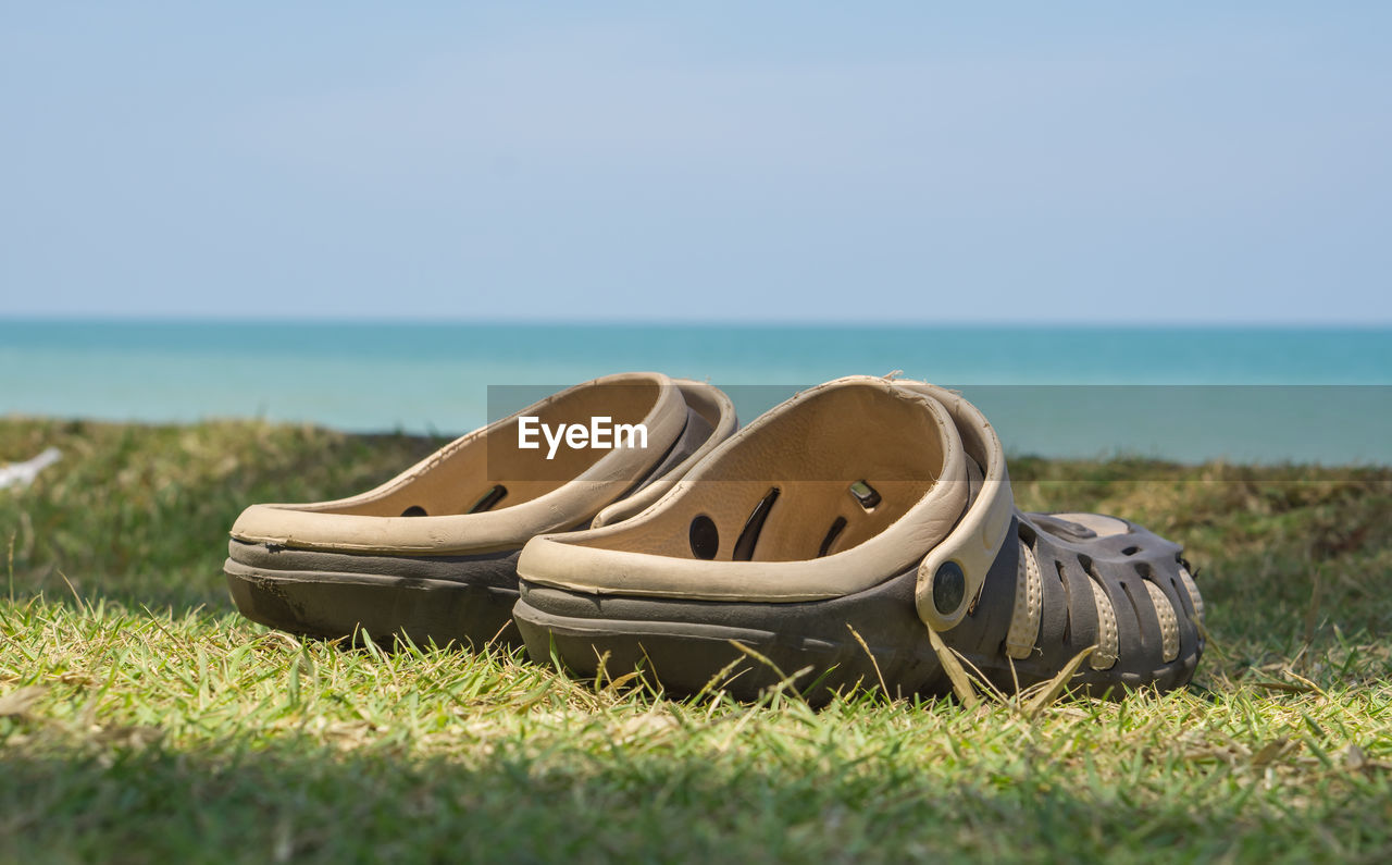 Abandoned shoes on grass by sea against sky