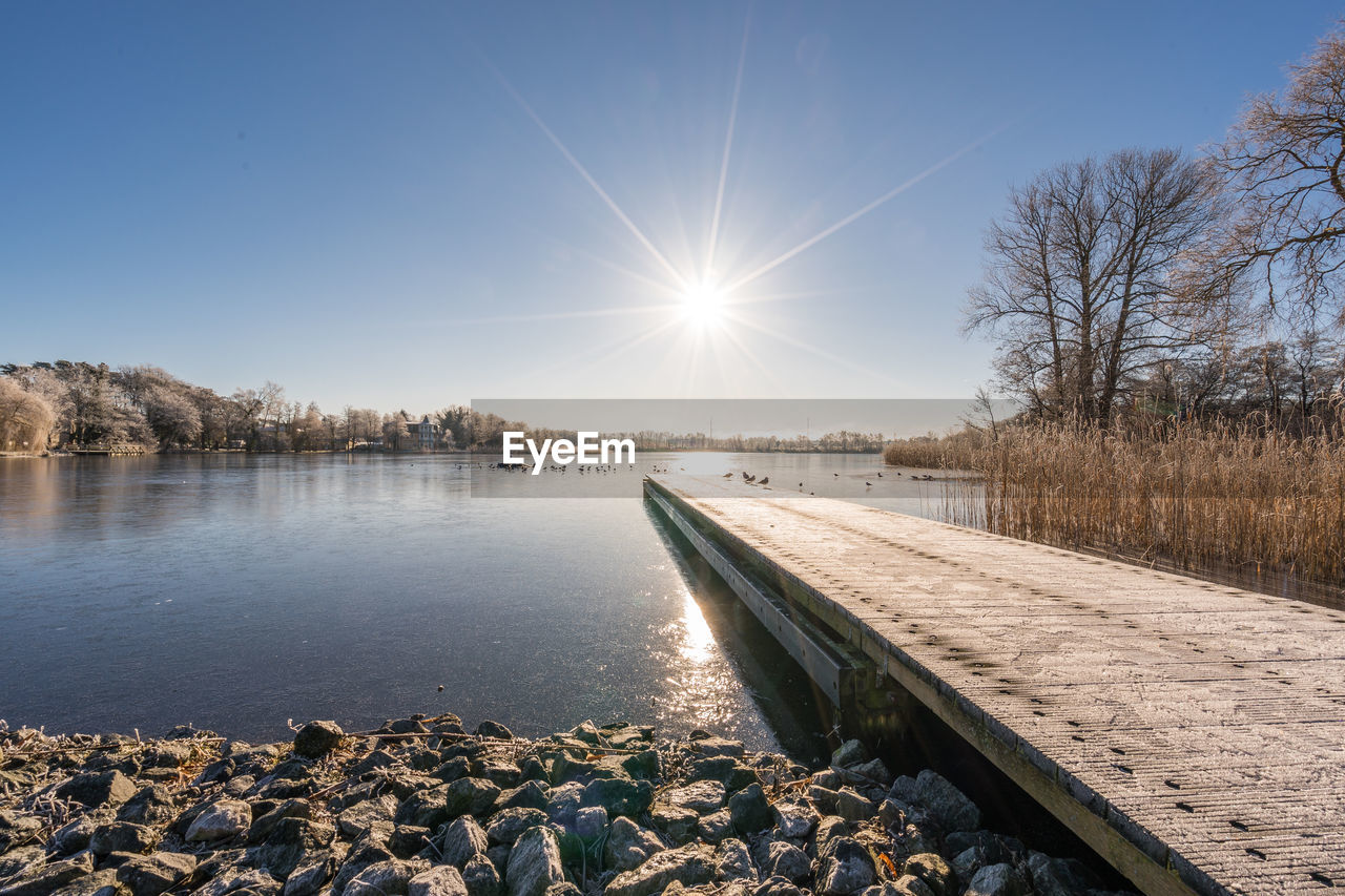 nature, sun, beauty in nature, tranquil scene, sunlight, tranquility, lens flare, no people, scenics, water, outdoors, cold temperature, sky, bare tree, winter, day, clear sky, tree