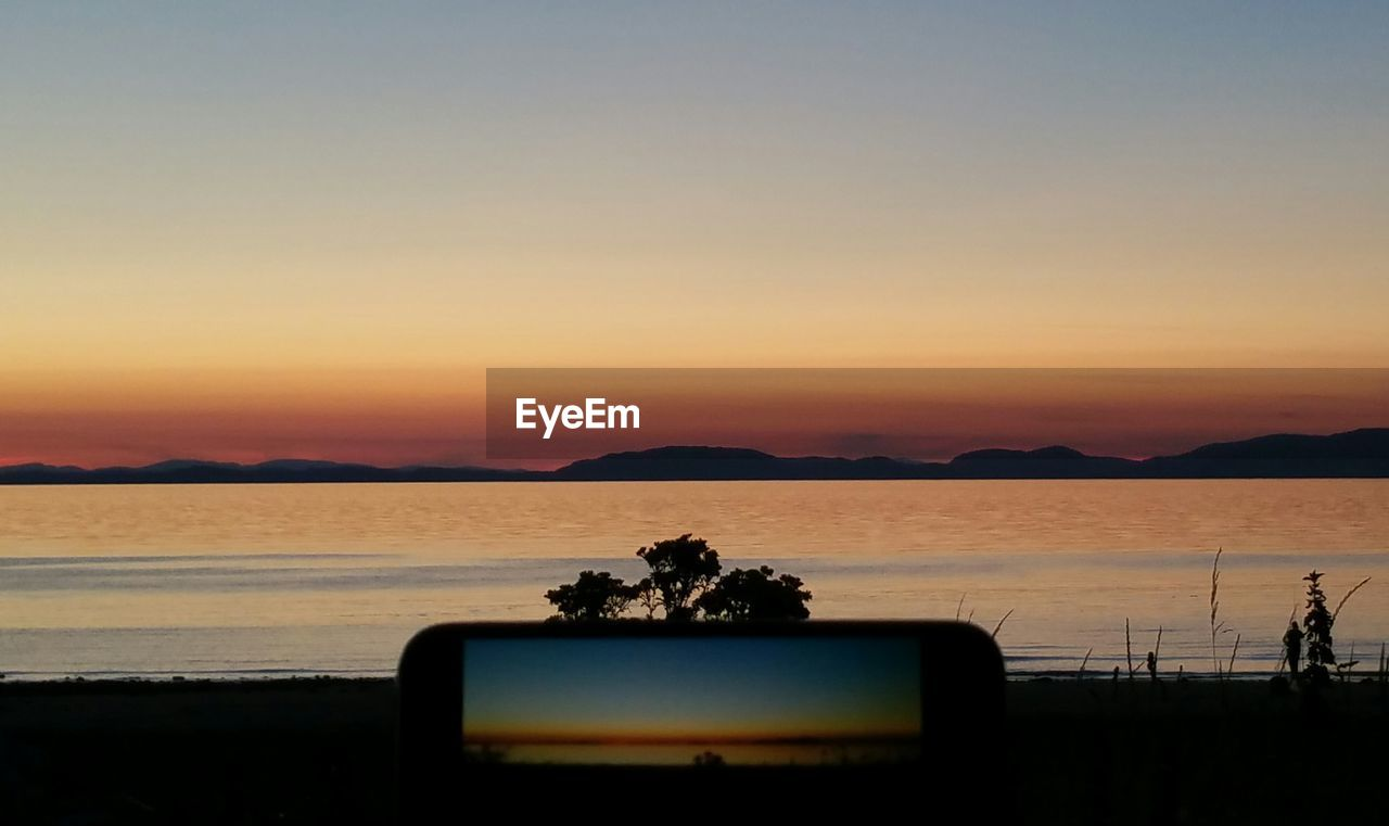 sunset, beauty in nature, nature, sea, orange color, silhouette, scenics, water, sky, tranquility, photographing, clear sky, technology, leisure, beach, wireless technology, no people, photography themes, horizon over water, mountain, outdoors