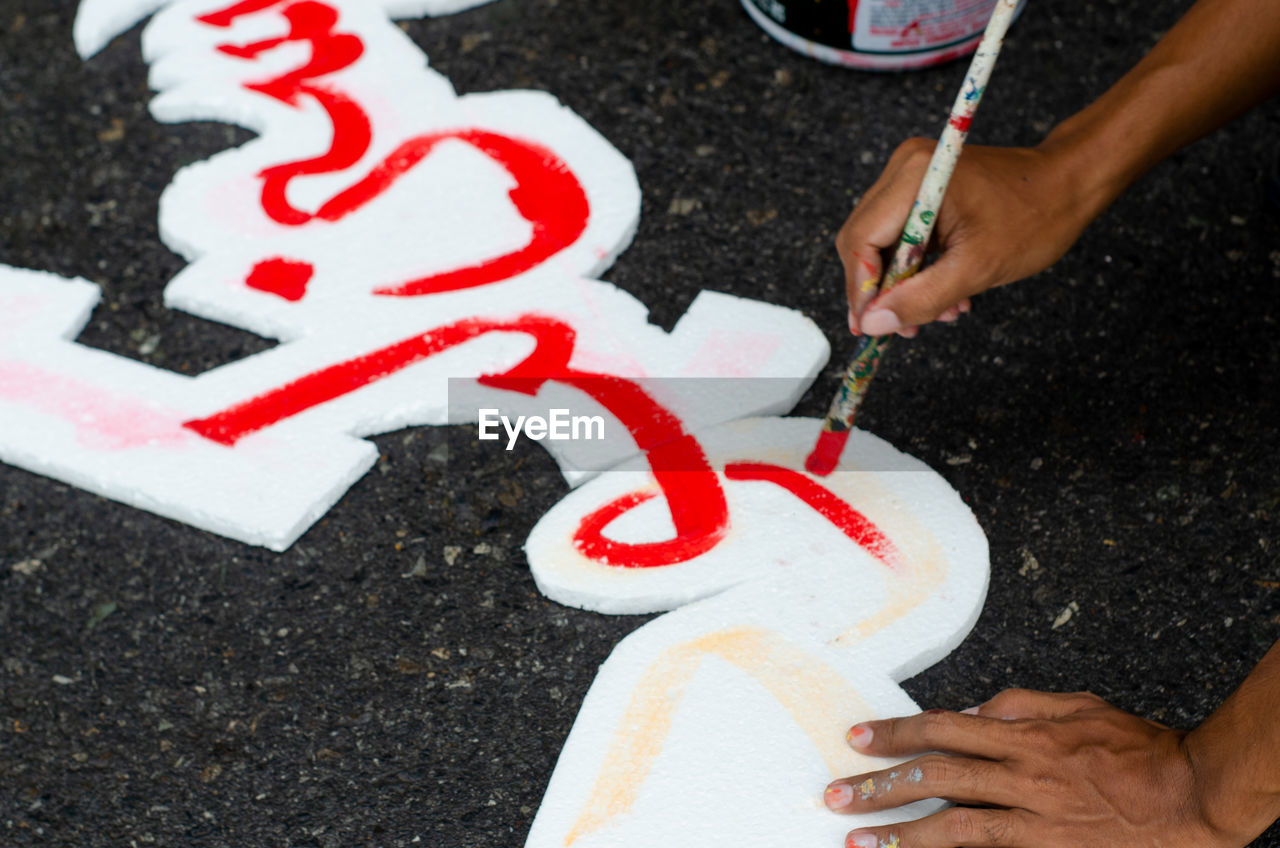 High angle view of hands painting on polystyrene