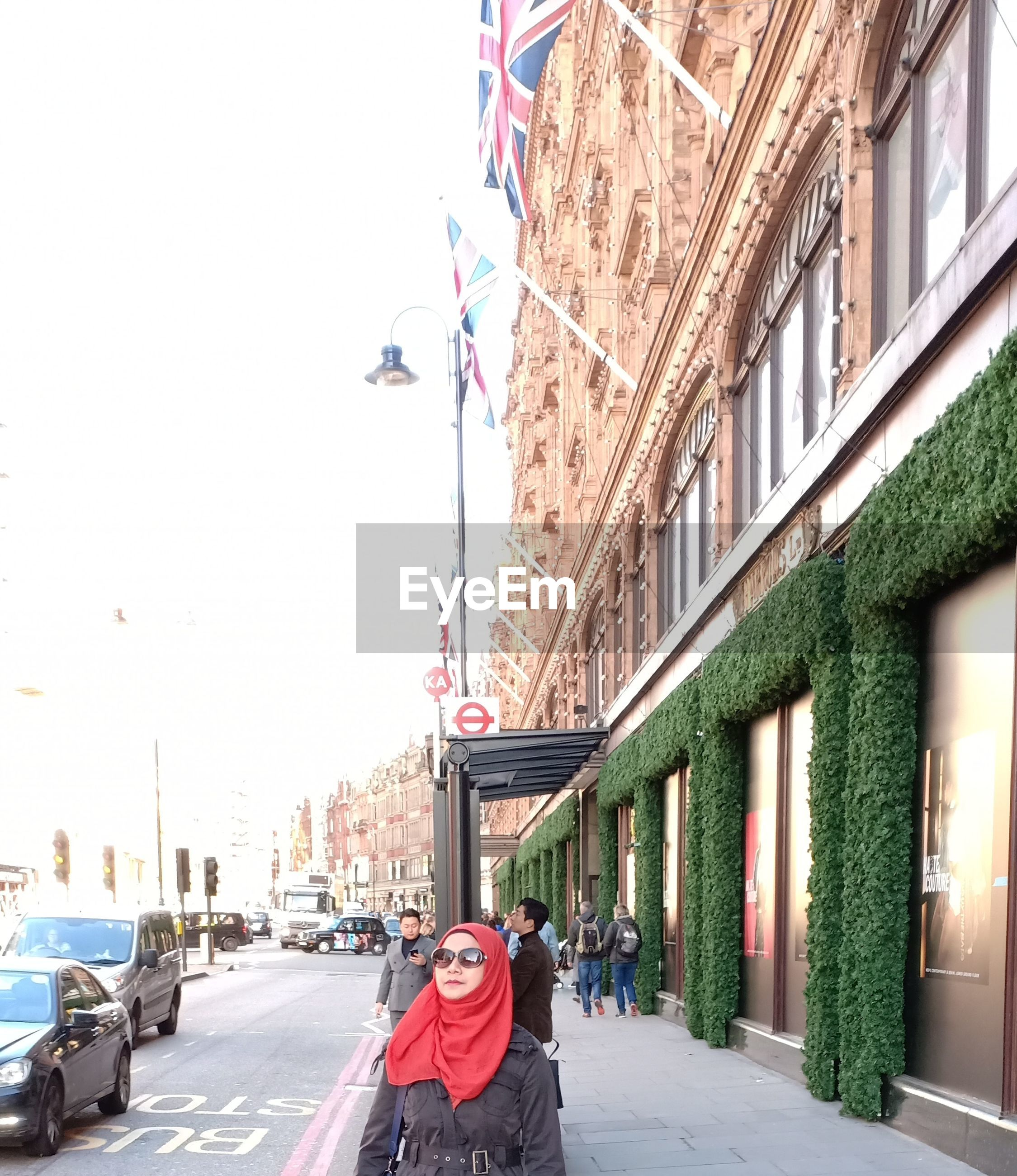 Mature woman wearing sunglasses while standing on city street amidst buildings against sky